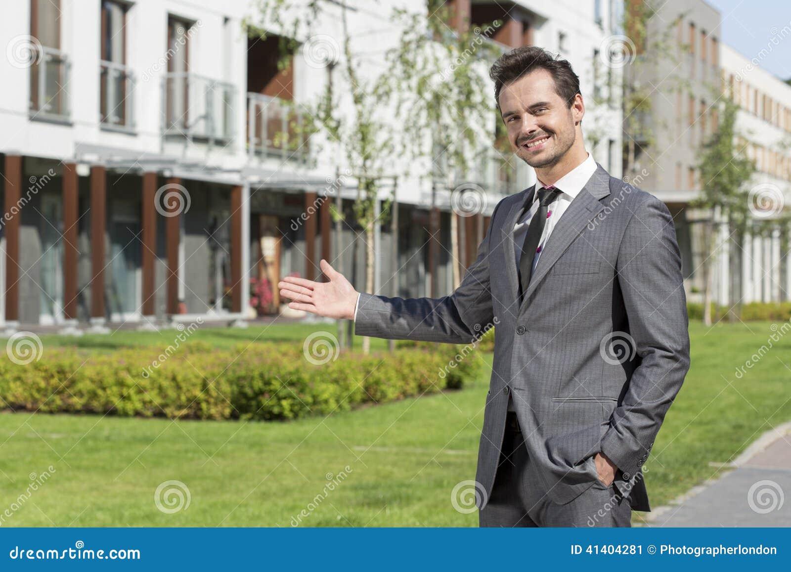 Retrato do mediador imobiliário seguro que apresenta o prédio de escritórios