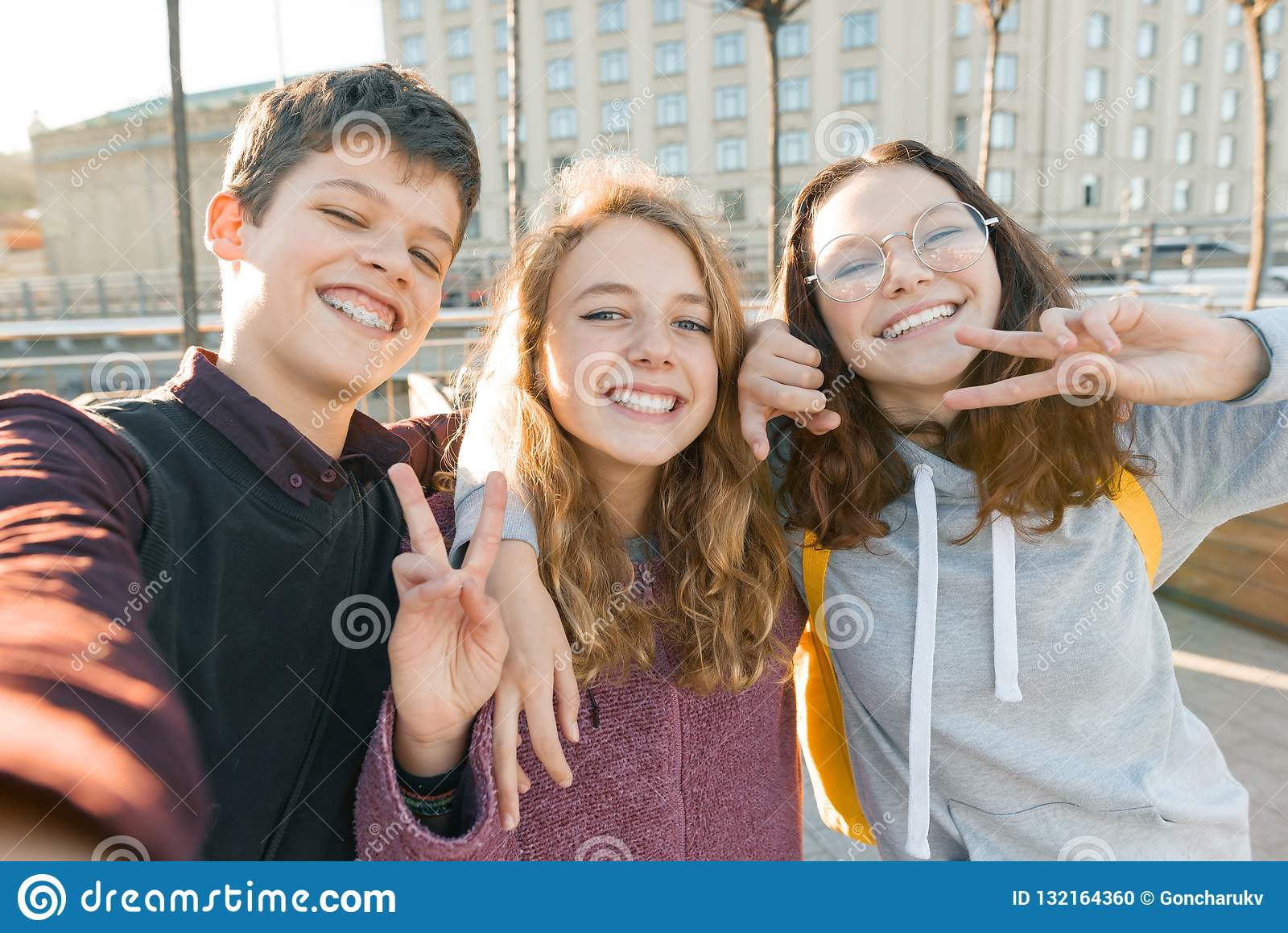 Retrato do menino adolescente de três amigos e duas das meninas que sorriem e que tomam um selfie fora Fundo da cidade, hora dour