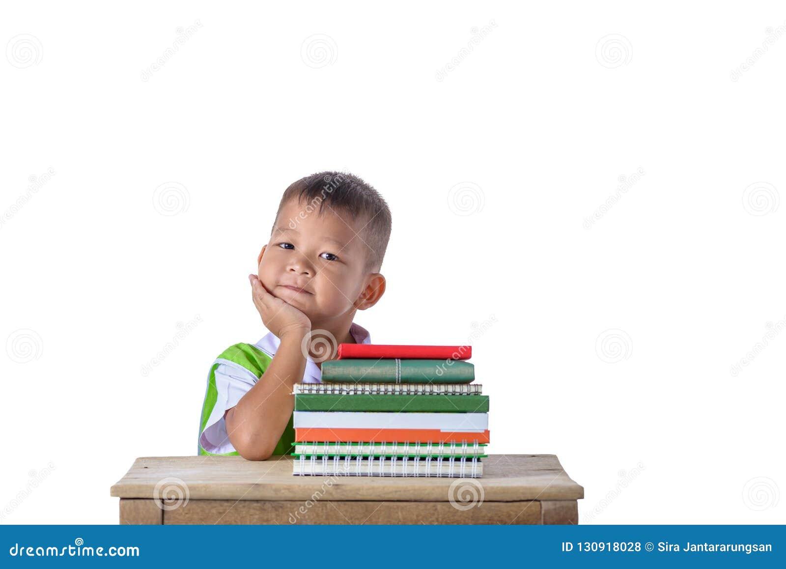 Retrato do menino asiático de sorriso do estudante pequeno com o edu de muitos livros
