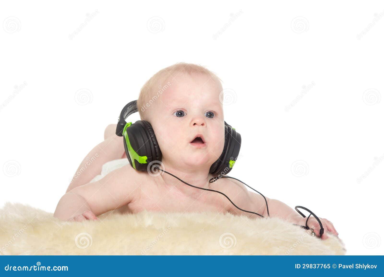 Retrato do menino do bebê de seis meses com auscultadores