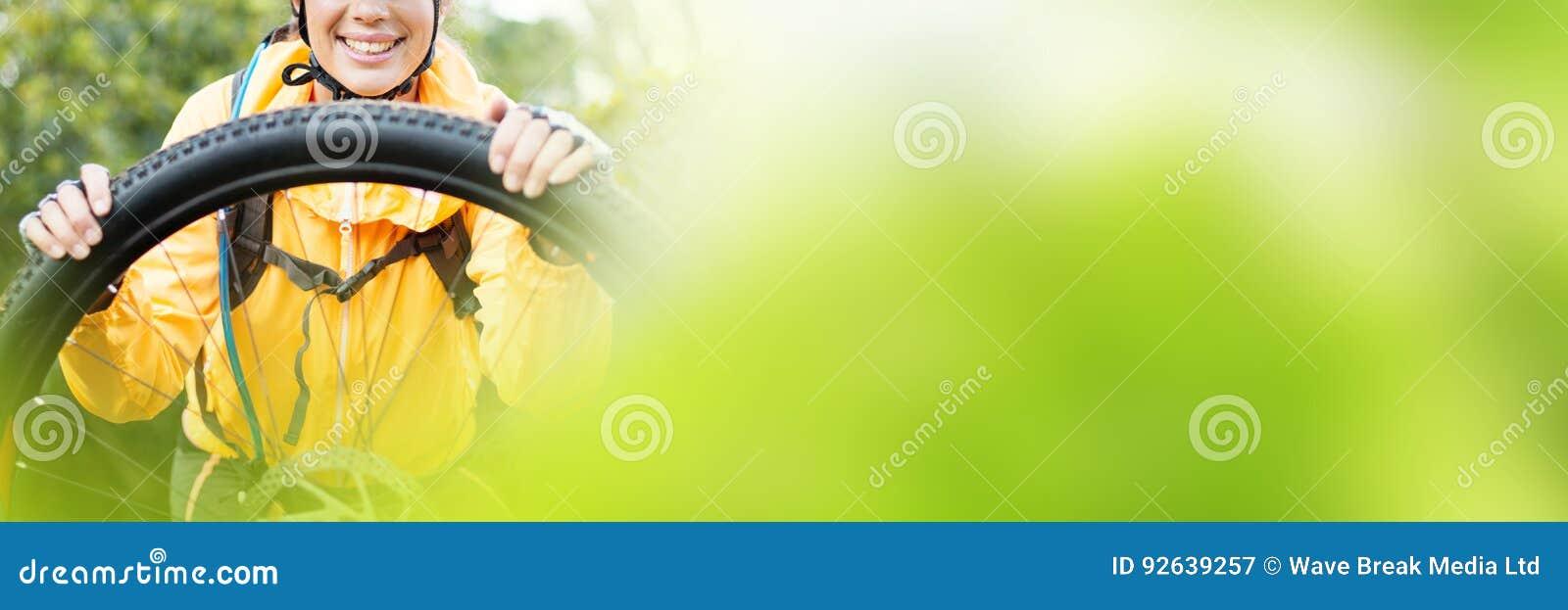 Retrato do motociclista fêmea que repara o Mountain bike