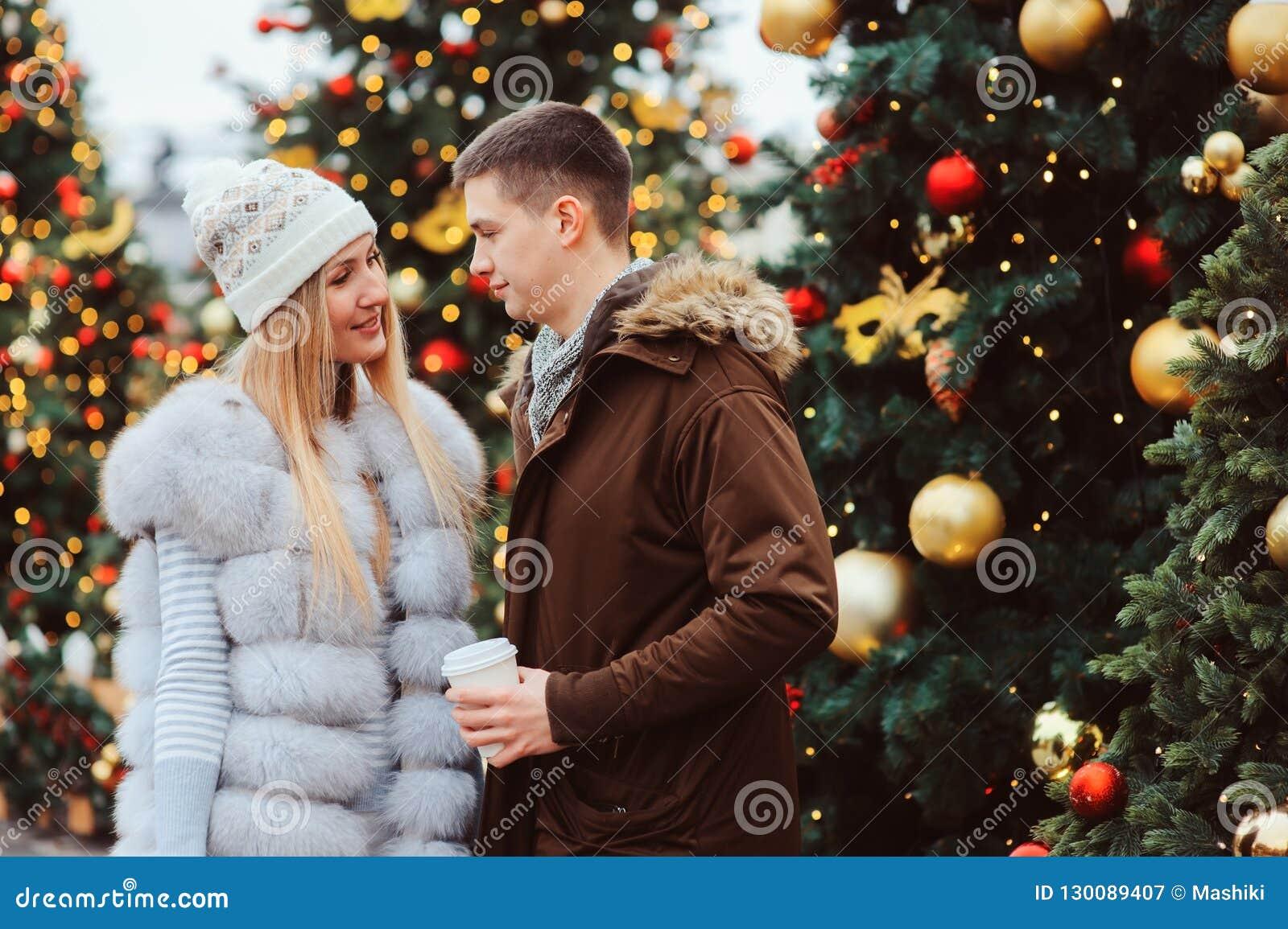Retrato do Natal de pares felizes com o vinho ou o chá ferventado com especiarias quente que andam nas ruas da cidade decoradas p