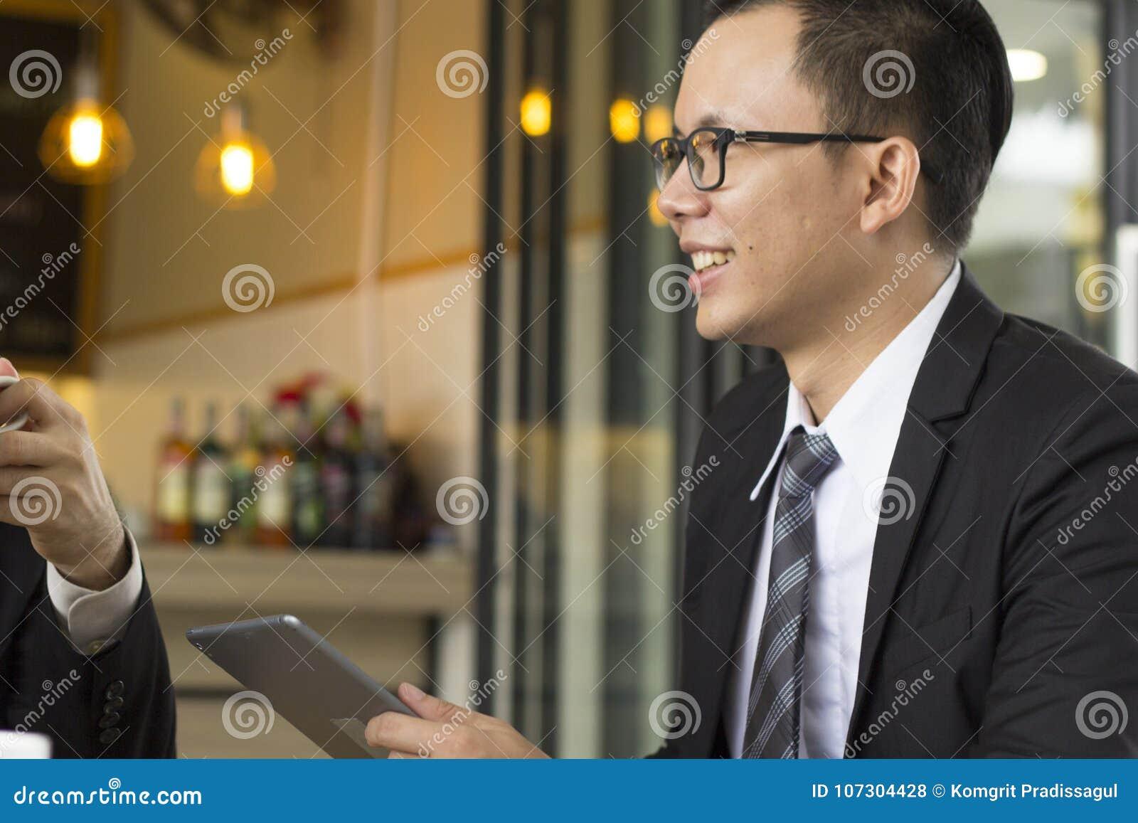 Retrato do negócio novo seguro que senta-se na tabela no encontro exterior, guardando o relatório comercial na tabuleta e no sorr