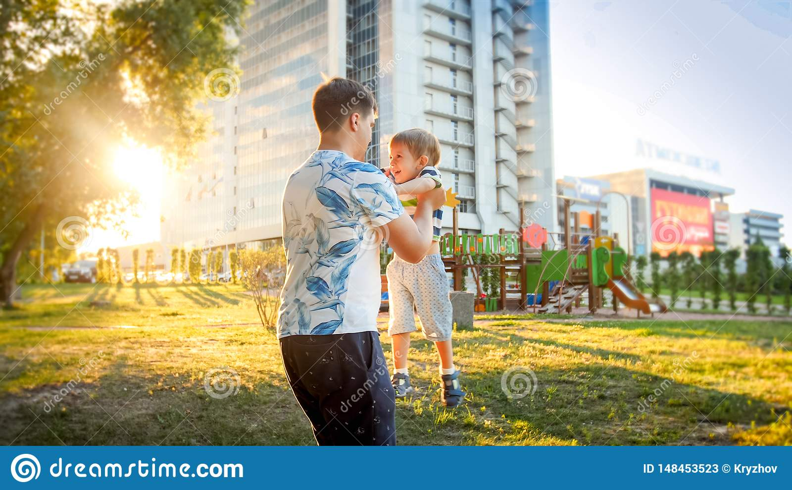 Retrato do pai novo feliz que abraça e que gerencie seu filho pequeno de sorriso da criança no parque