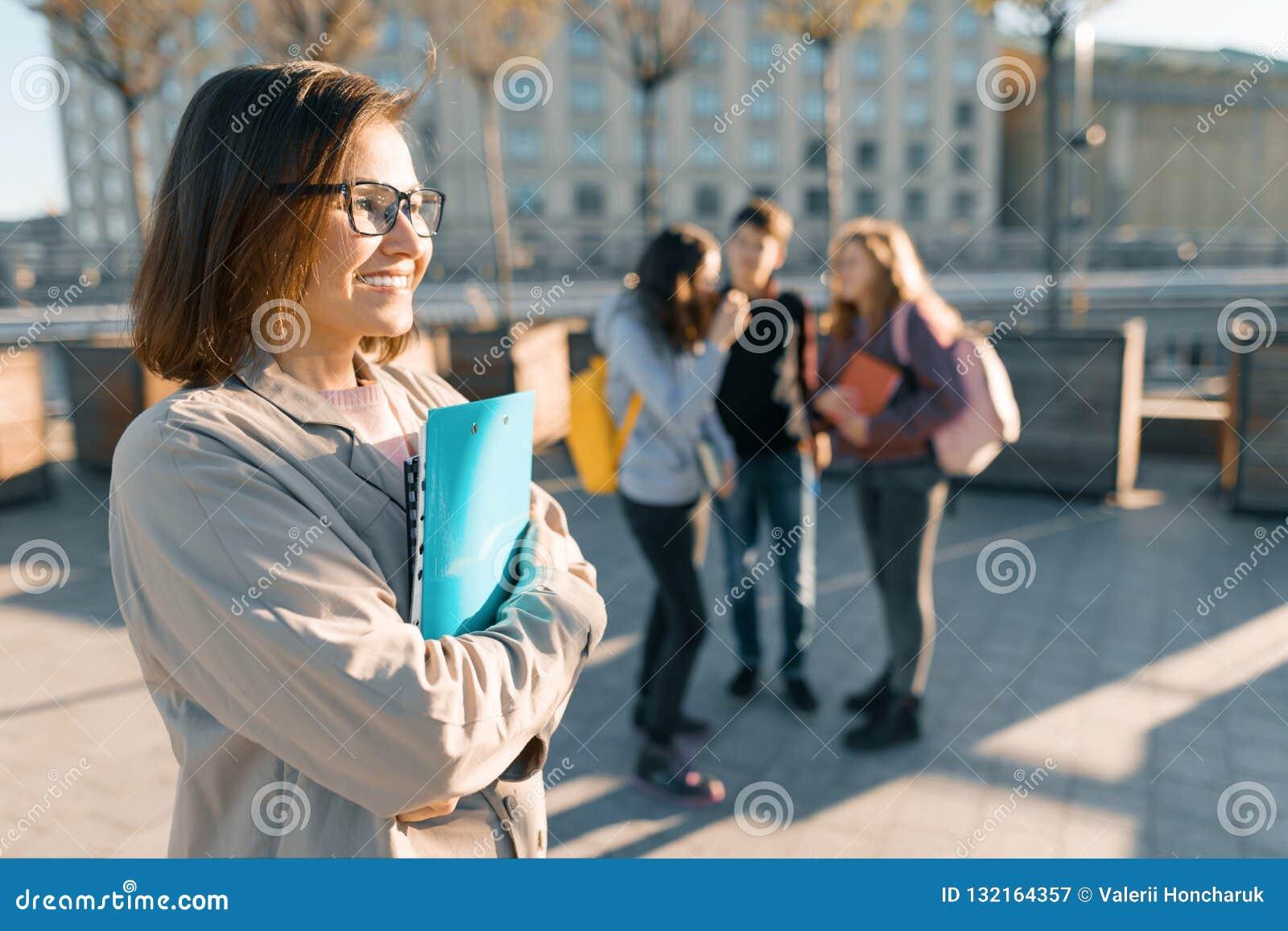 Retrato do professor fêmea de sorriso maduro nos vidros com prancheta, outdor com um grupo de estudantes dos adolescentes, hora d