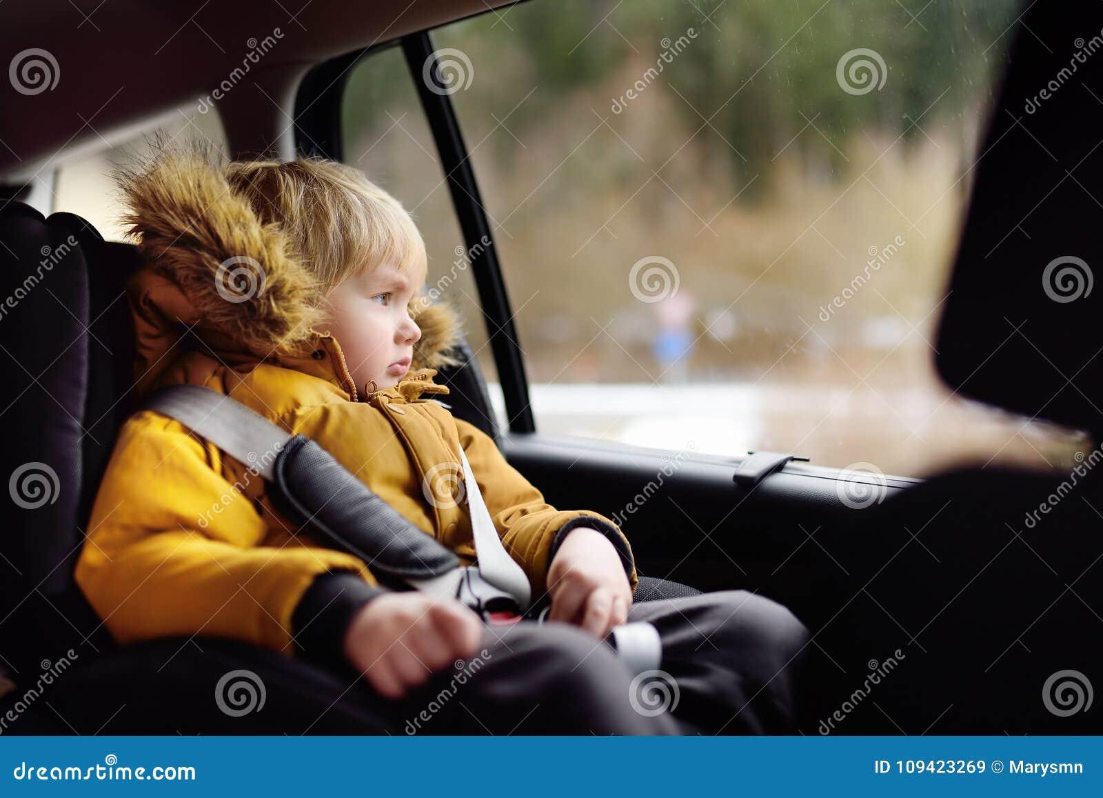 Retrato do rapaz pequeno bonito que senta-se no banco de carro durante o roadtrip ou o curso