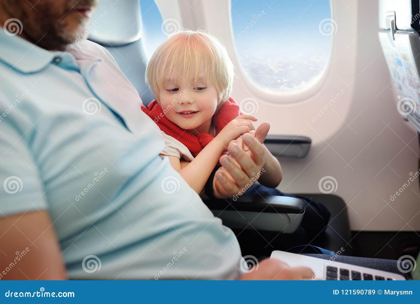 Retrato do rapaz pequeno com seu pai durante a viagem por um avião