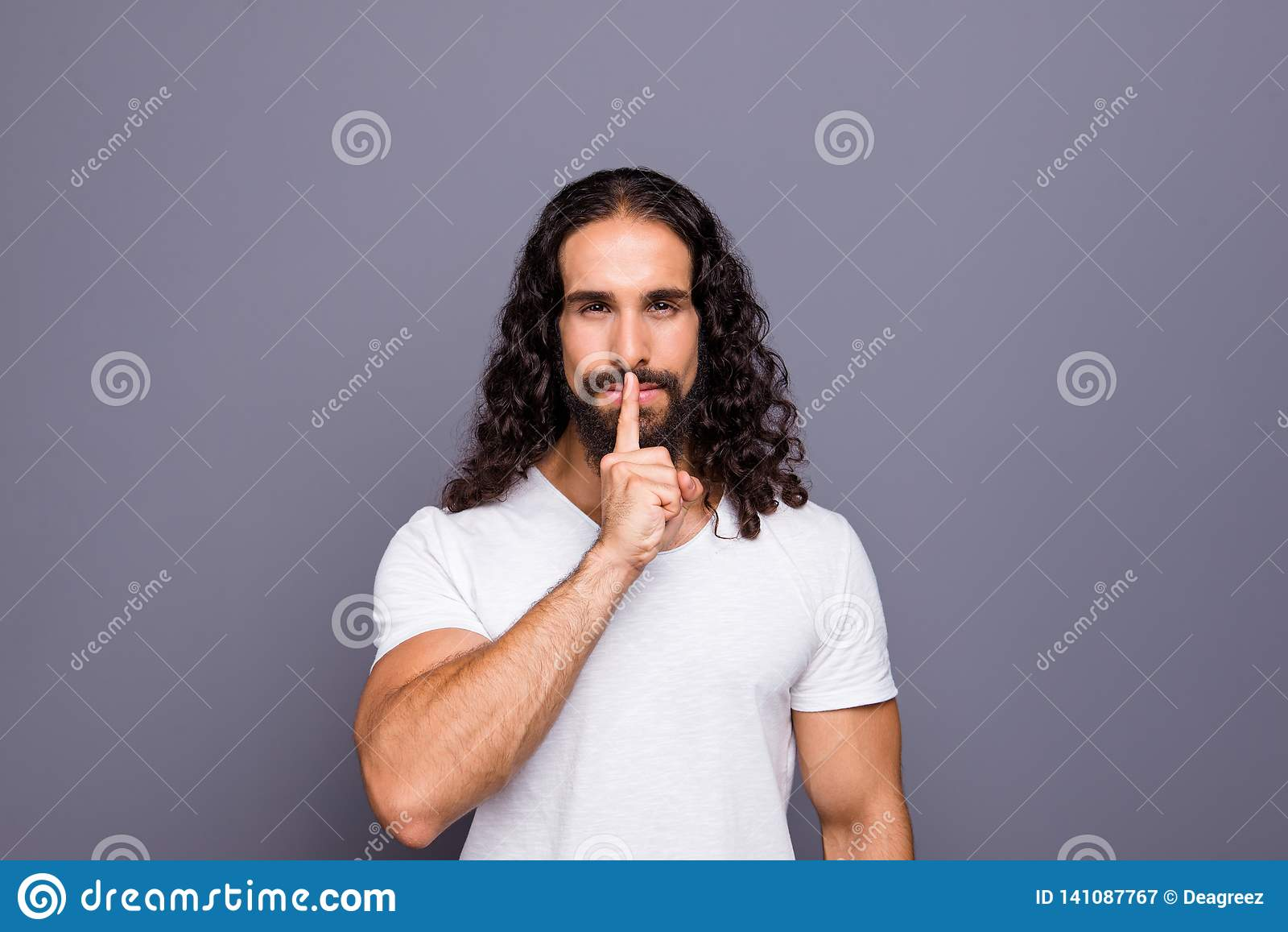 Retrato do seu ele indivíduo ondulado-de cabelo ocupado cândido atrativo preparado agradável que mostra shh o símbolo isolado sob