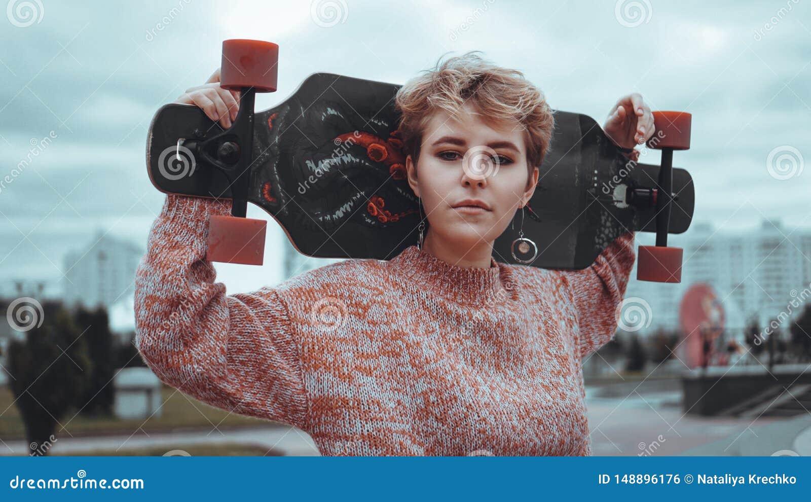 Retrato do skater f?mea novo que guarda seu skate