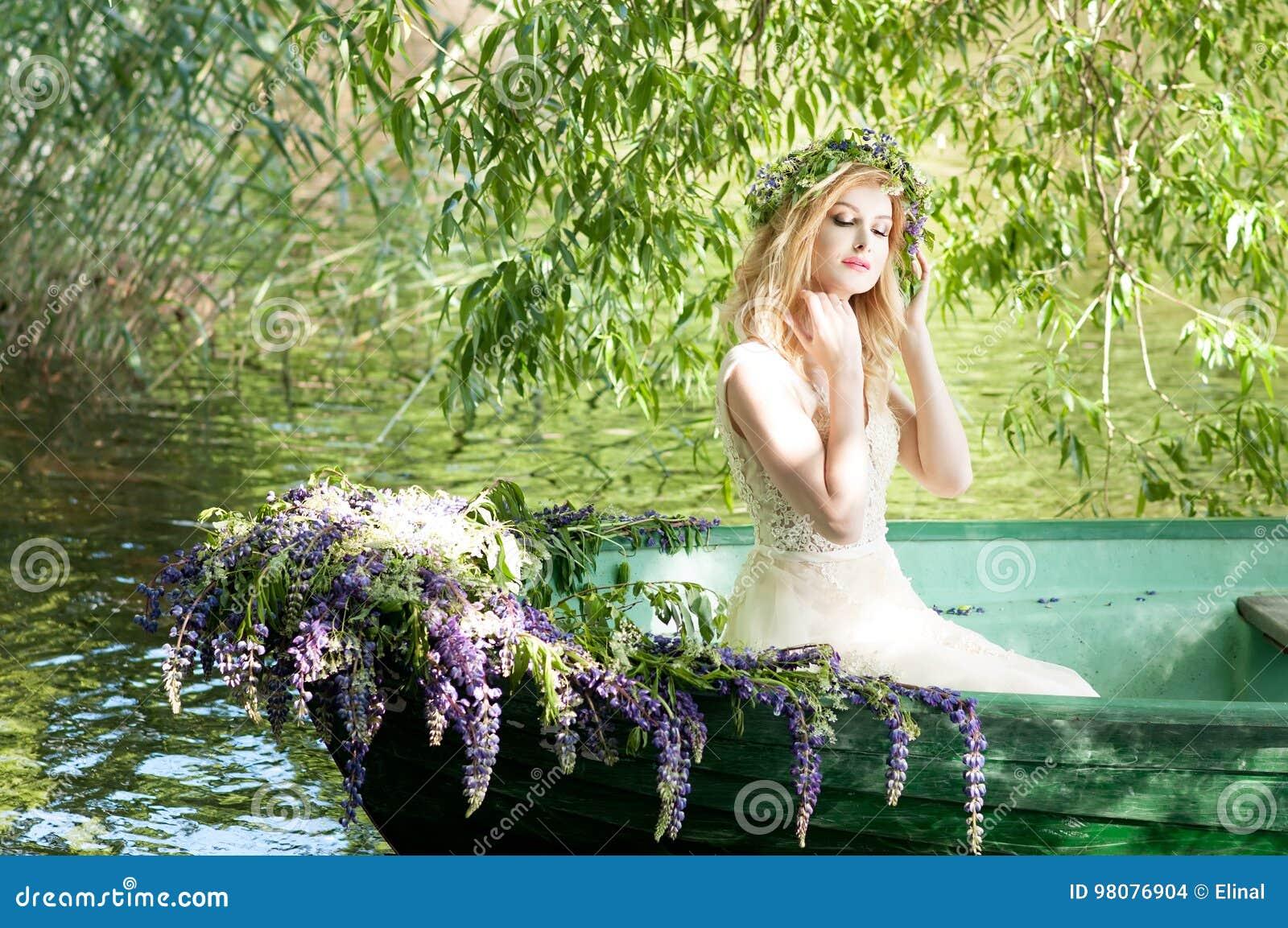 Retrato do slavic ou da mulher Báltico com a grinalda que senta-se no barco com flores verão
