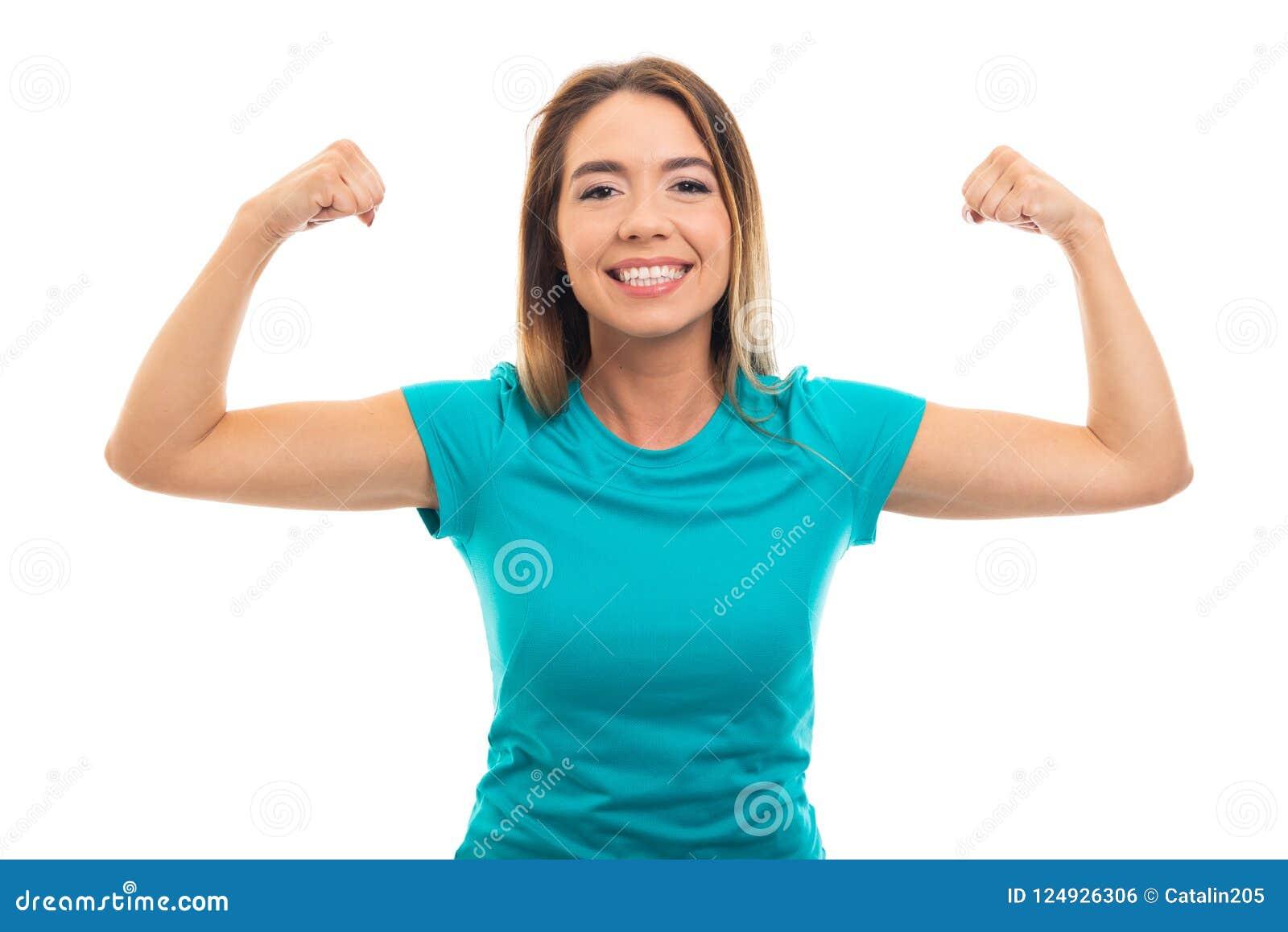 Retrato do t-shirt vestindo da menina bonita nova que dobra ges do bíceps