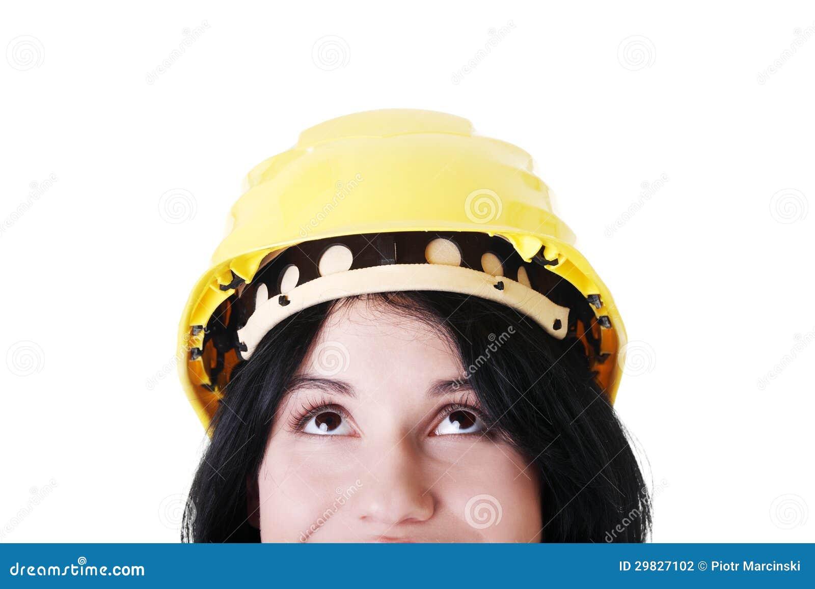 Retrato do trabalhador fêmea no capacete que olha acima.