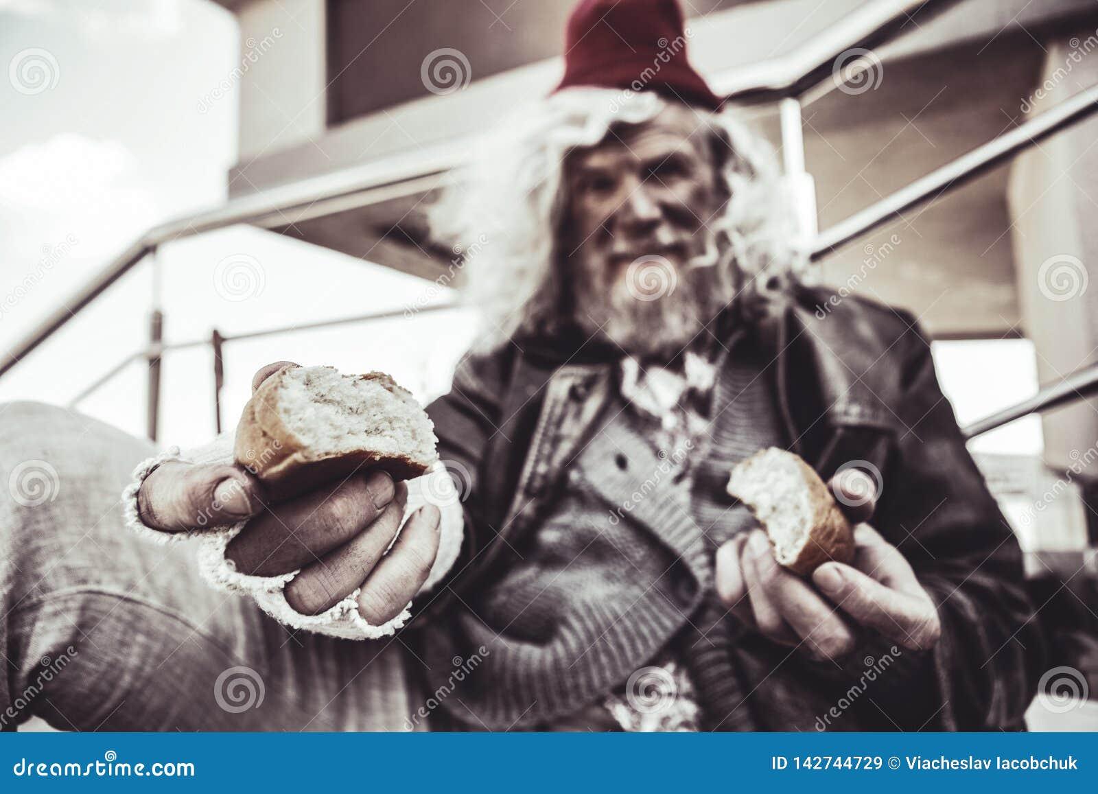 Retrato do vagabundo idoso que senta e que compartilha de seu bolo com o desconhecido