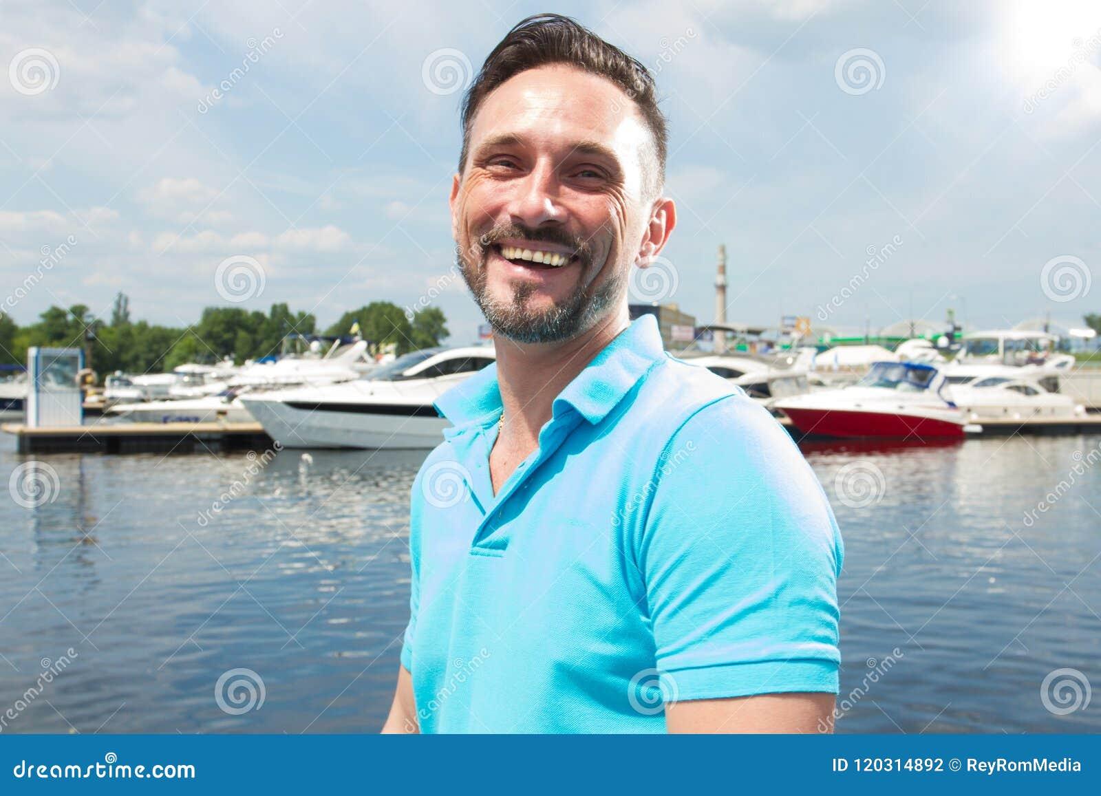 Retrato do  yachtsman  feliz de sorriso no porto com fundo do barco Tempo da vela das férias de verão para o estilo de vida mascu