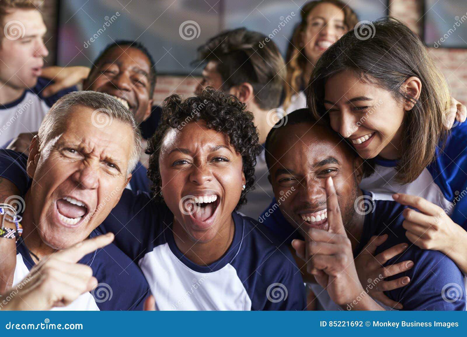 Retrato dos amigos que olham o jogo na barra de esportes em telas