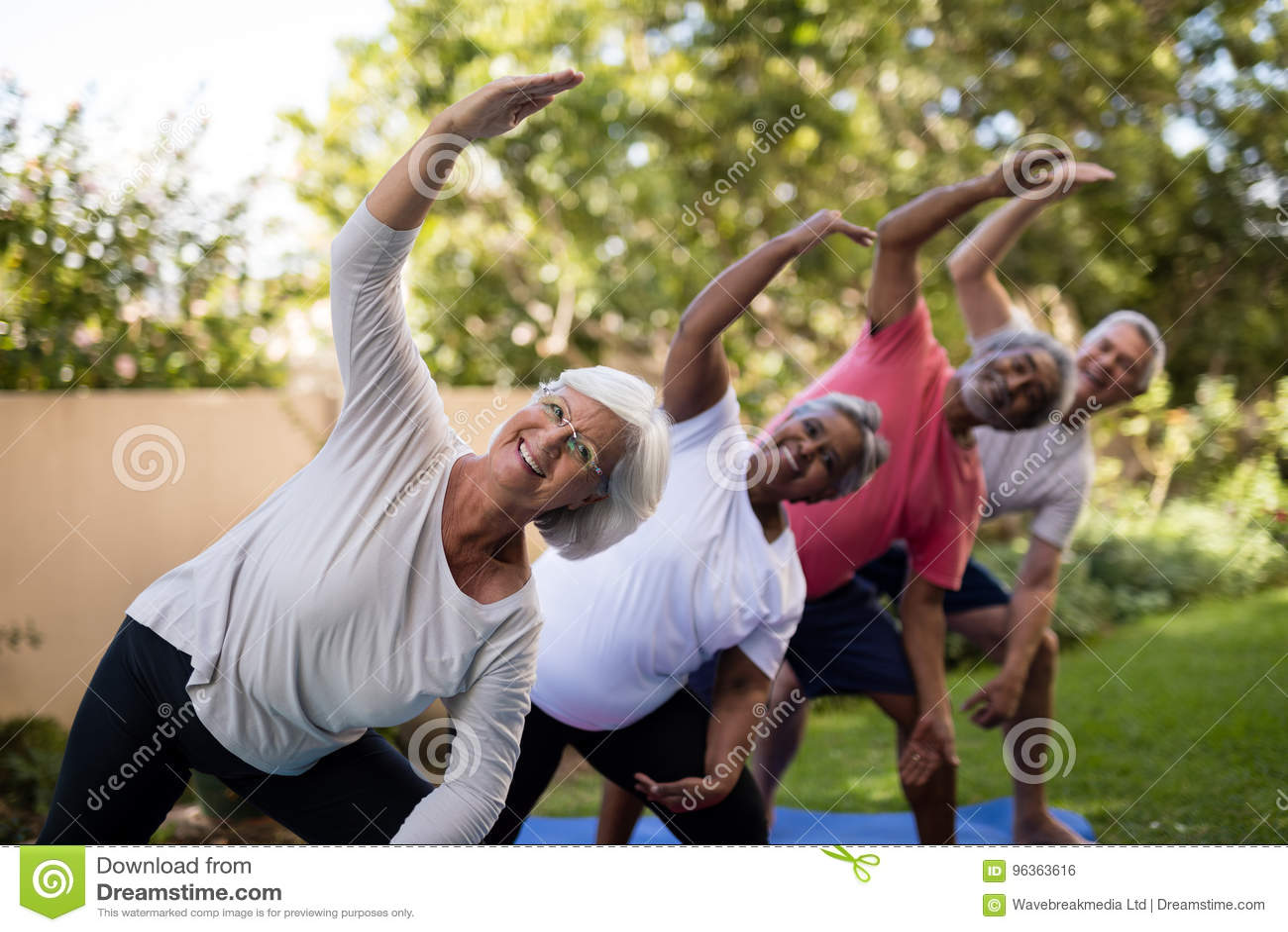 Retrato dos amigos superiores de sorriso que exercitam com os braços aumentados
