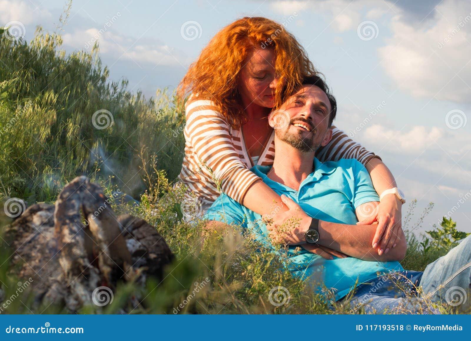 Retrato dos pares felizes que colocam na cobertura na grama perto da chaminé no fundo das nuvens