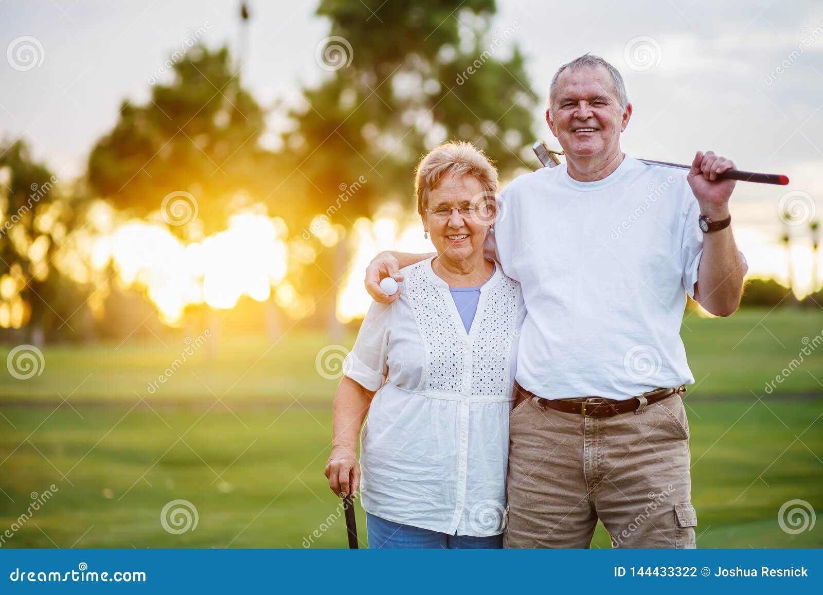 Retrato dos pares superiores felizes que apreciam o estilo de vida ativo que joga o golfe