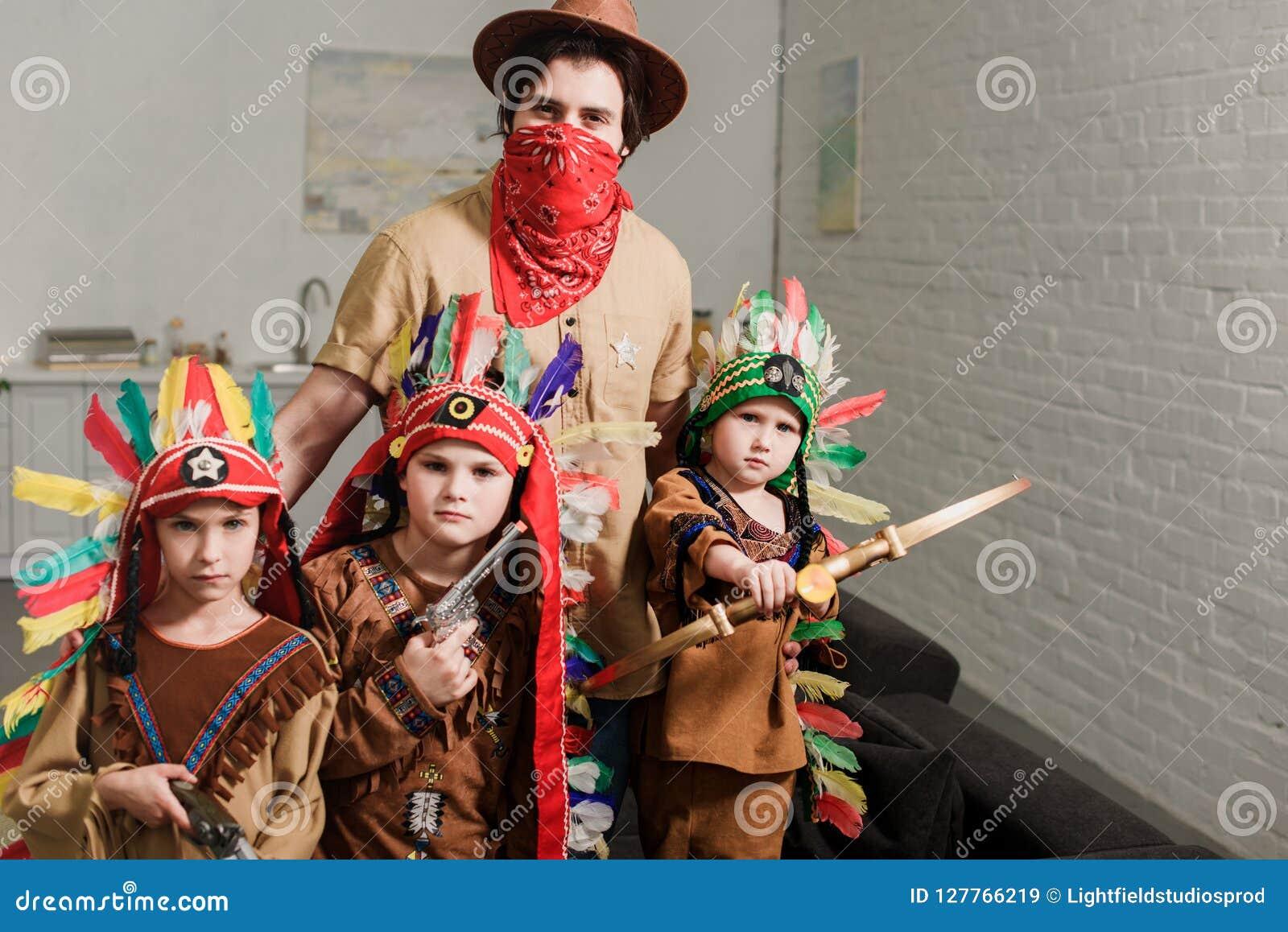 Retrato dos rapazes pequenos em trajes e no pai nativos no chapéu e do bandana vermelho que olha a câmera