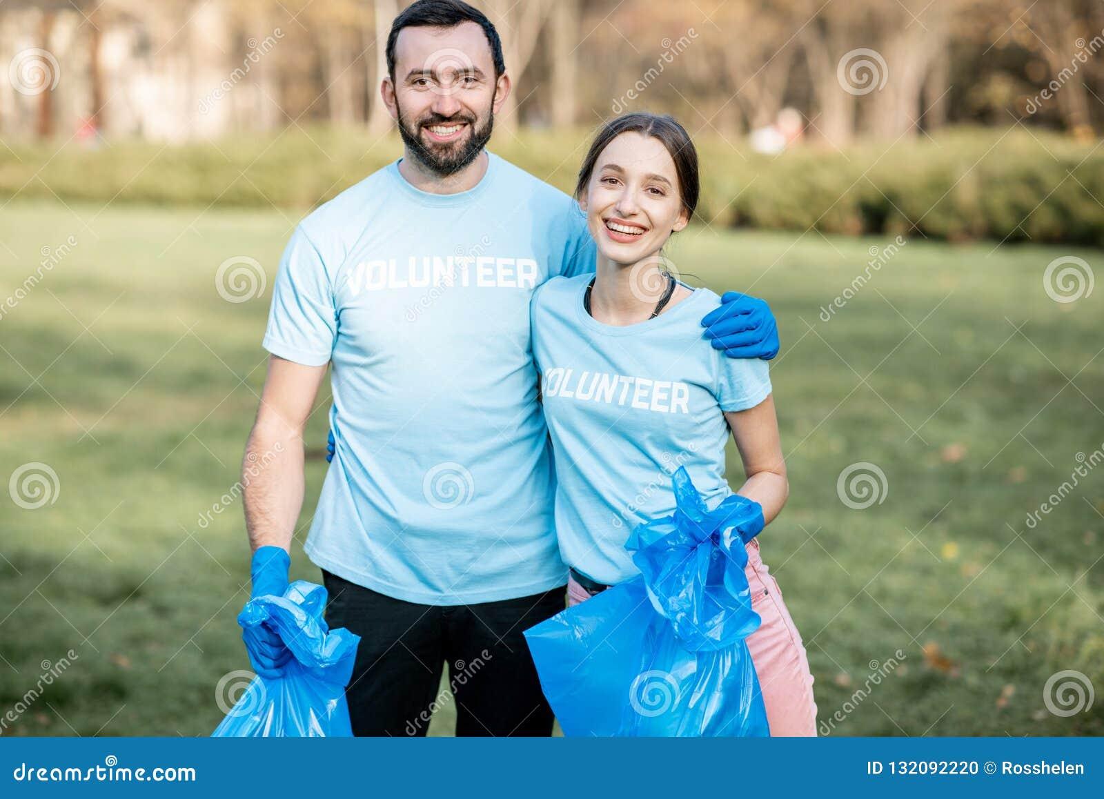 Retrato dos voluntários com os sacos dos desperdícios no parque