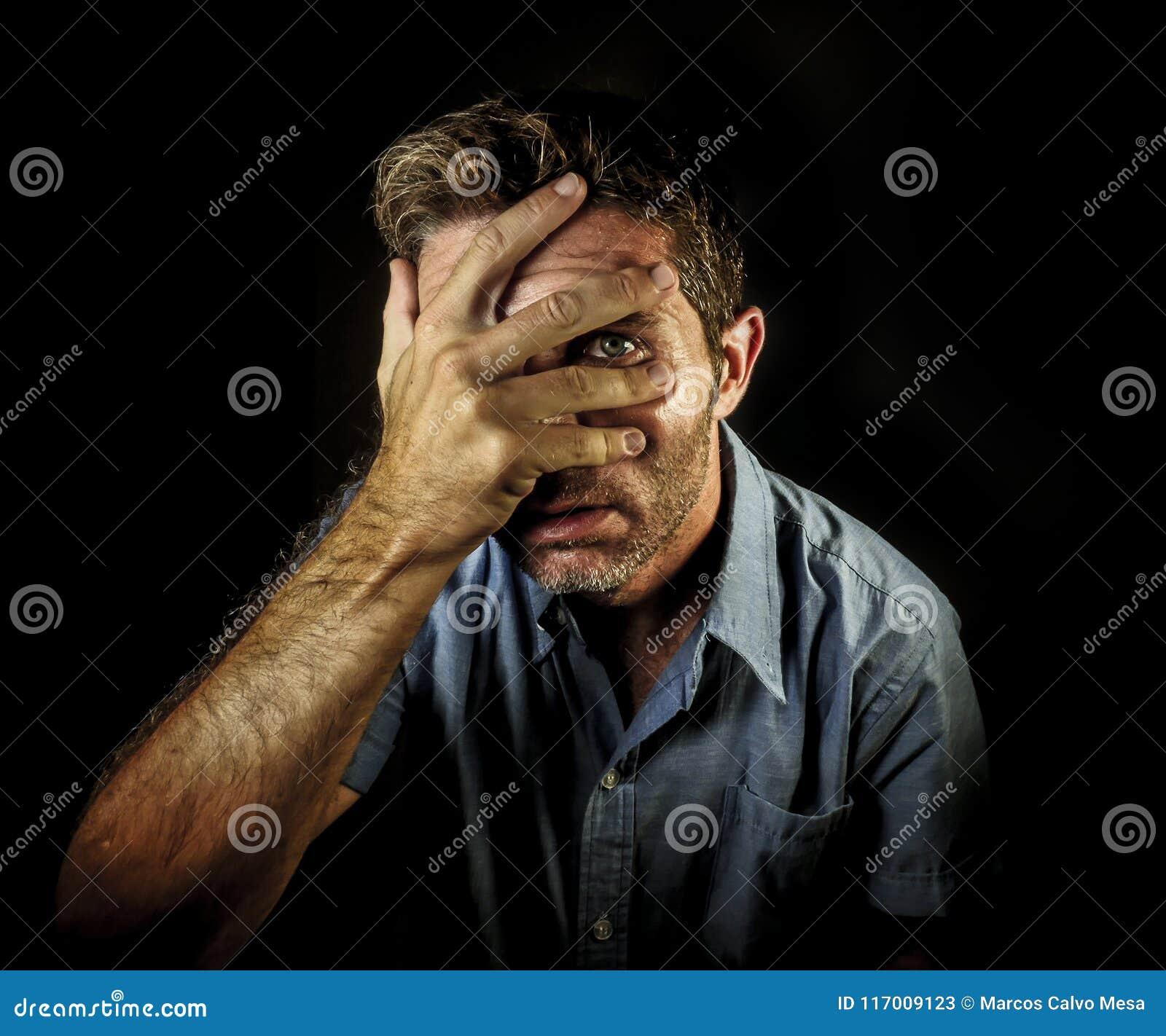 Retrato dramático de la cara atractiva joven de la cubierta del hombre con las manos pero los fingeres de la abertura a ver y el