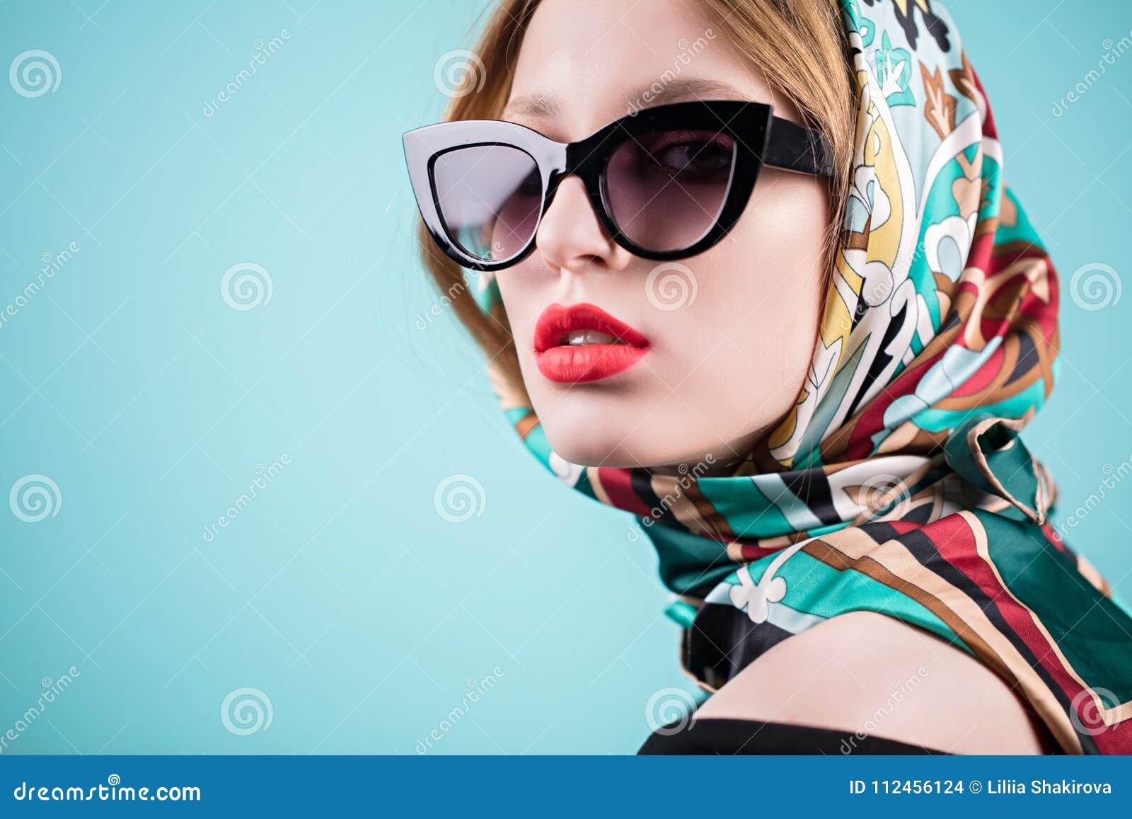 0469d3afa Retrato elegante de uma jovem mulher à moda nos óculos de sol e no lenço,  isolado no fundo azul