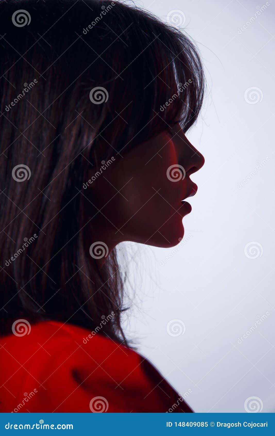 Retrato en perfil un modelo moreno atractivo, con los labios grandes en traje rojo, peinado elegante, aislado en un fondo blanco