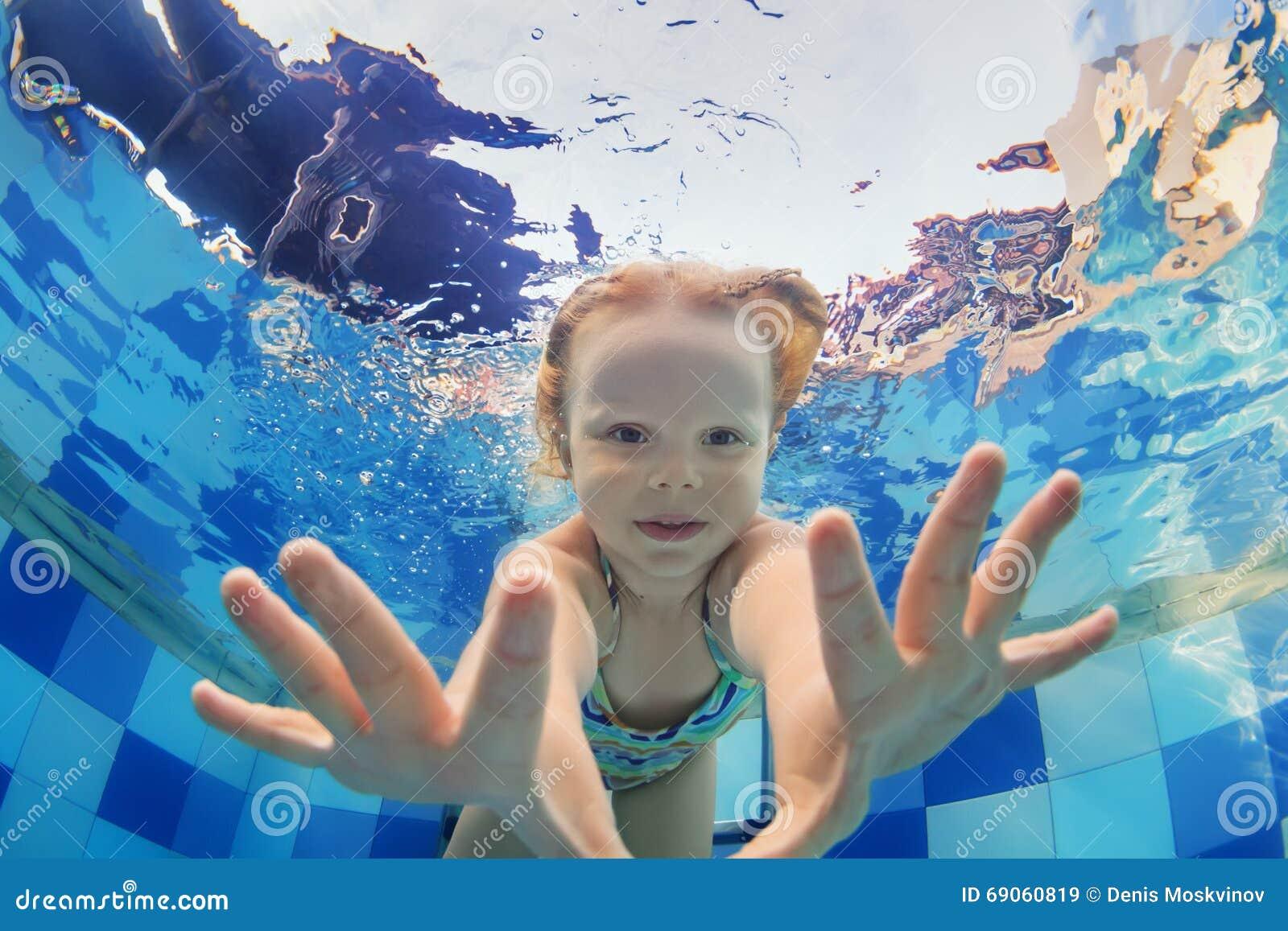 Retrato engraçado do bebê que nada debaixo d água na associação