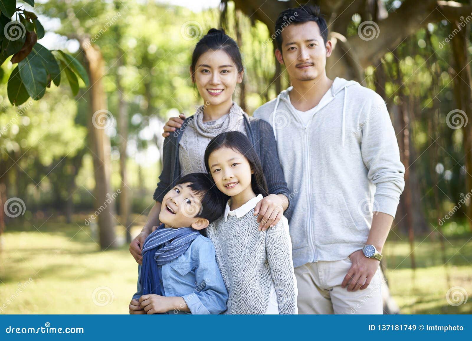 Retrato exterior da família asiática