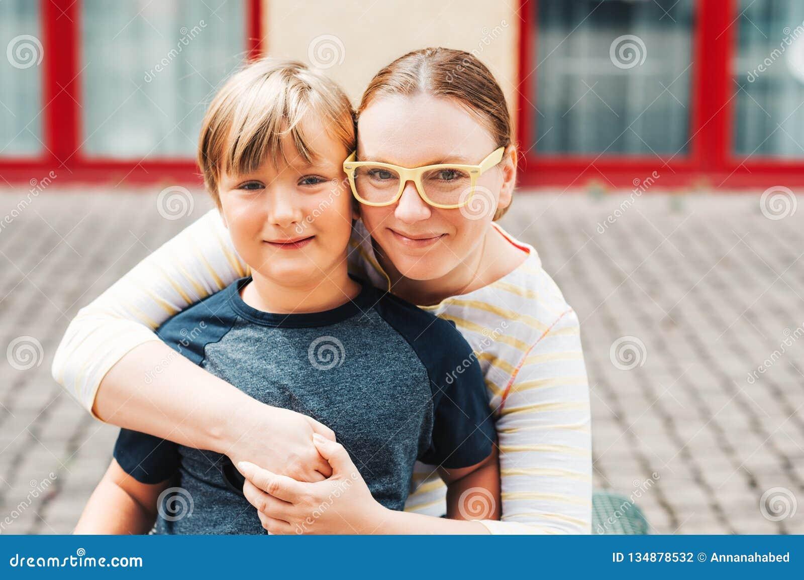 Retrato exterior da mãe feliz com filho bonito