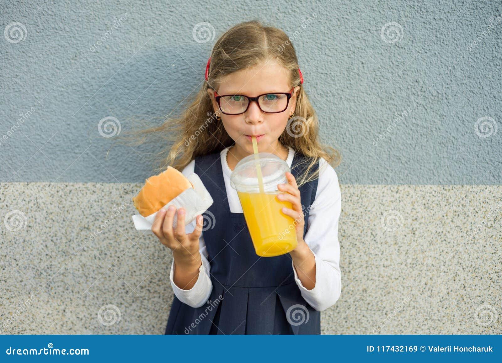 Retrato exterior da menina da criança com cabelo encaracolado louro com vidros A menina come o sanduíche e bebe o suco de laranja