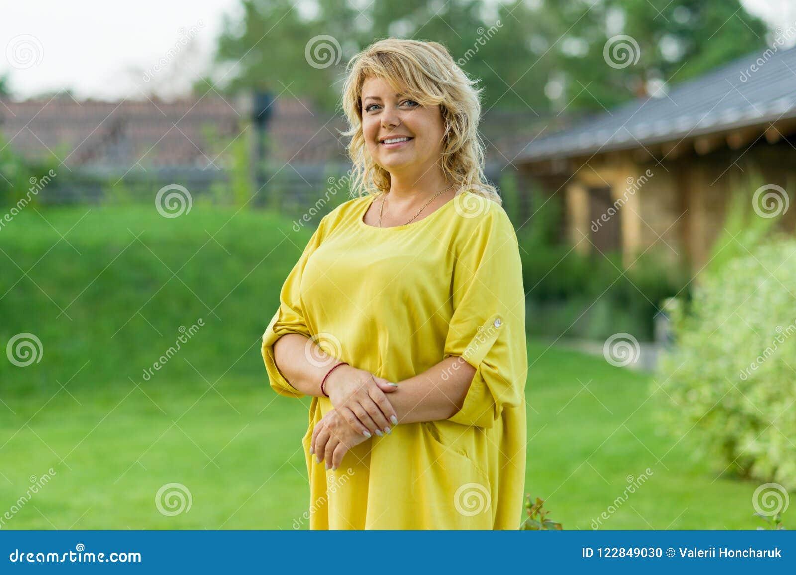 Retrato exterior da mulher de meia idade madura positiva, sorriso fêmea, jardim do fundo