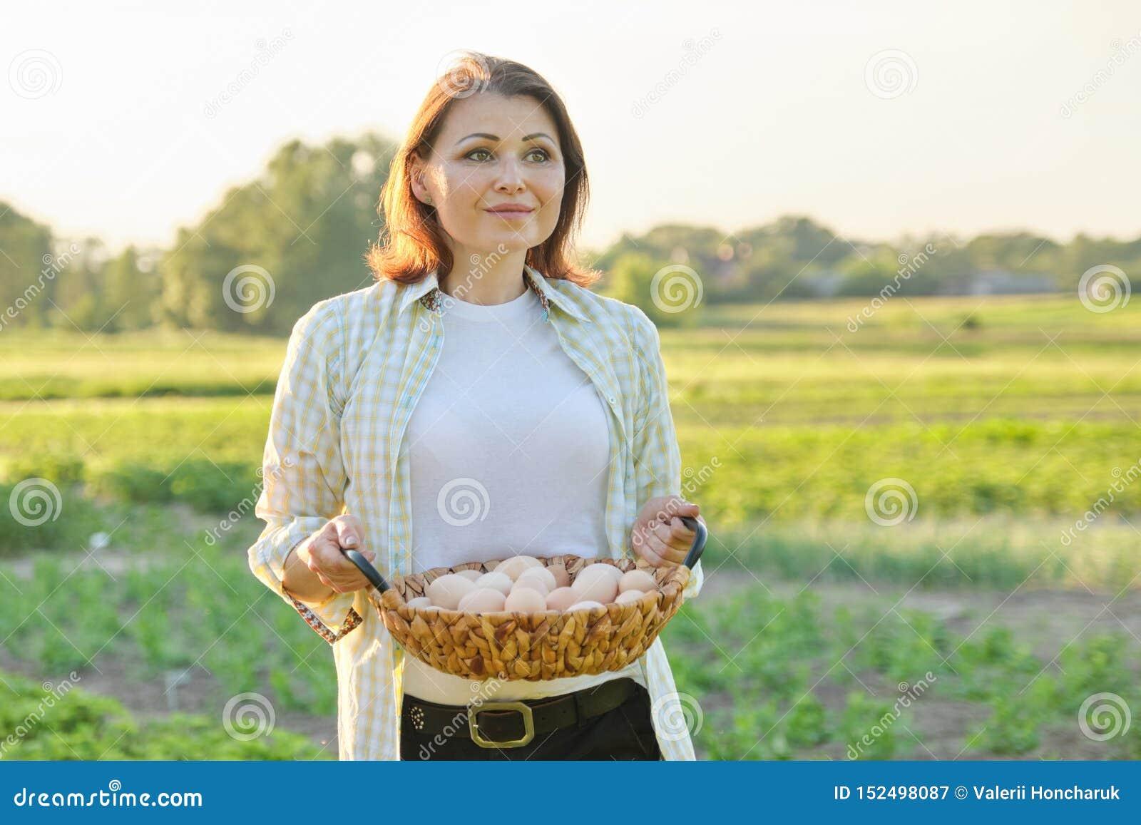 Retrato exterior da mulher do fazendeiro com a cesta de ovos frescos da galinha, exploração agrícola