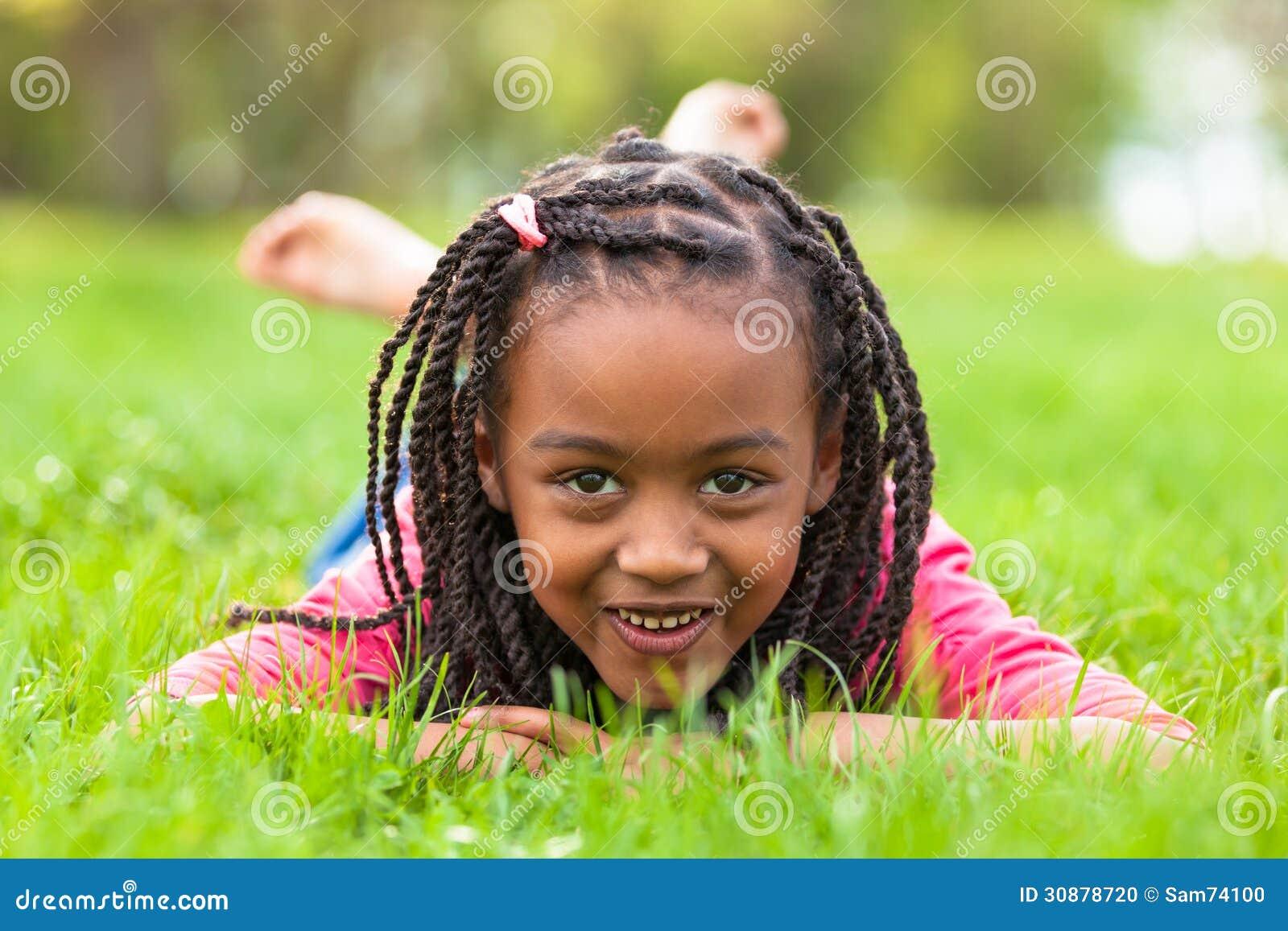 Retrato exterior de uma menina preta nova bonito que sorri - pe africano