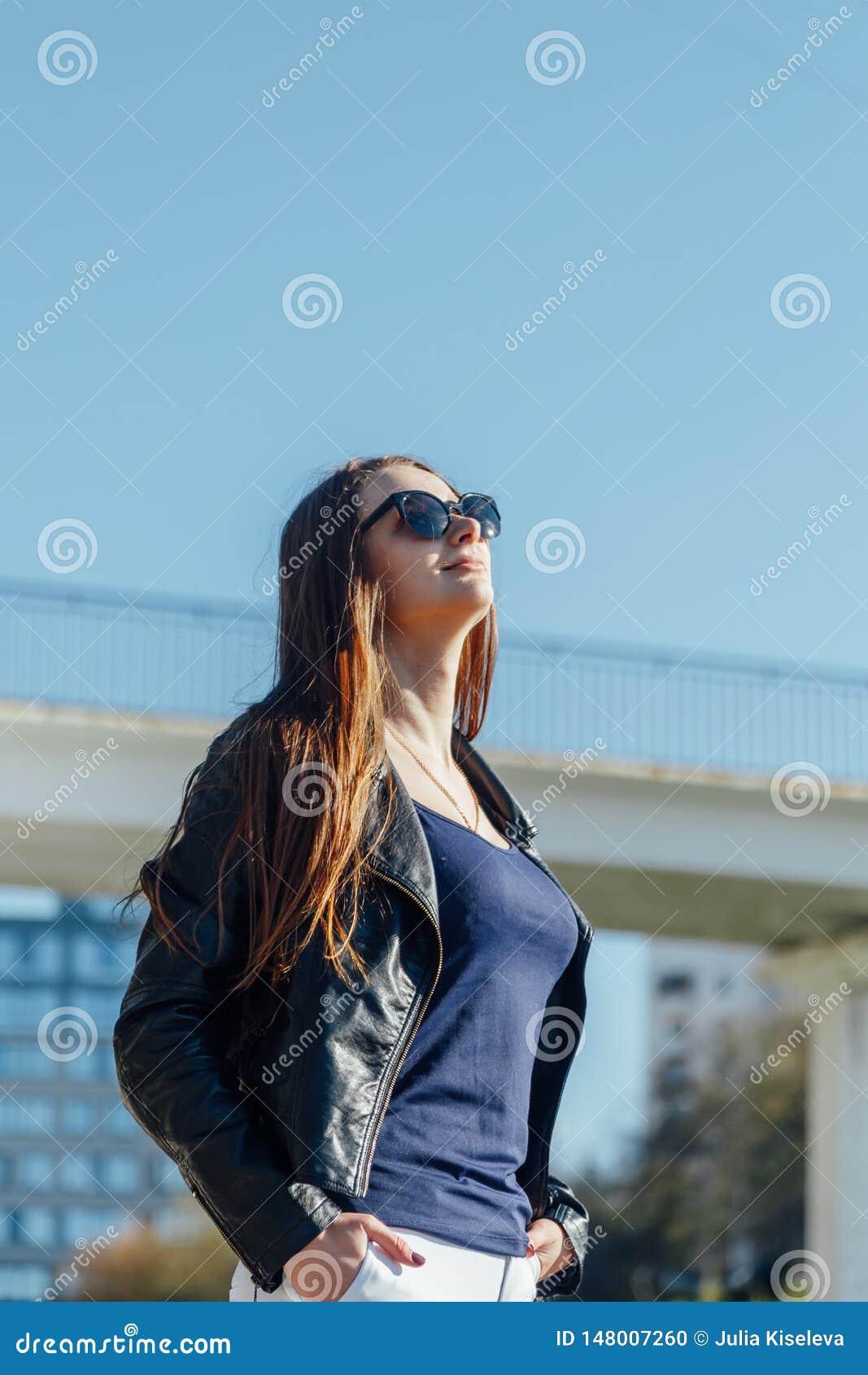 Retrato exterior de uma mulher segura bonita nova que levanta na rua