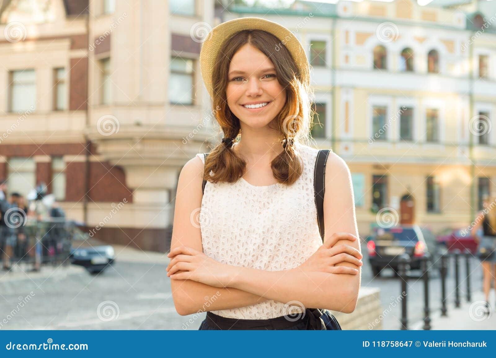 Retrato exterior do adolescente 13, 14 anos velhos, menina com braços cruzados, fundo da rua da cidade