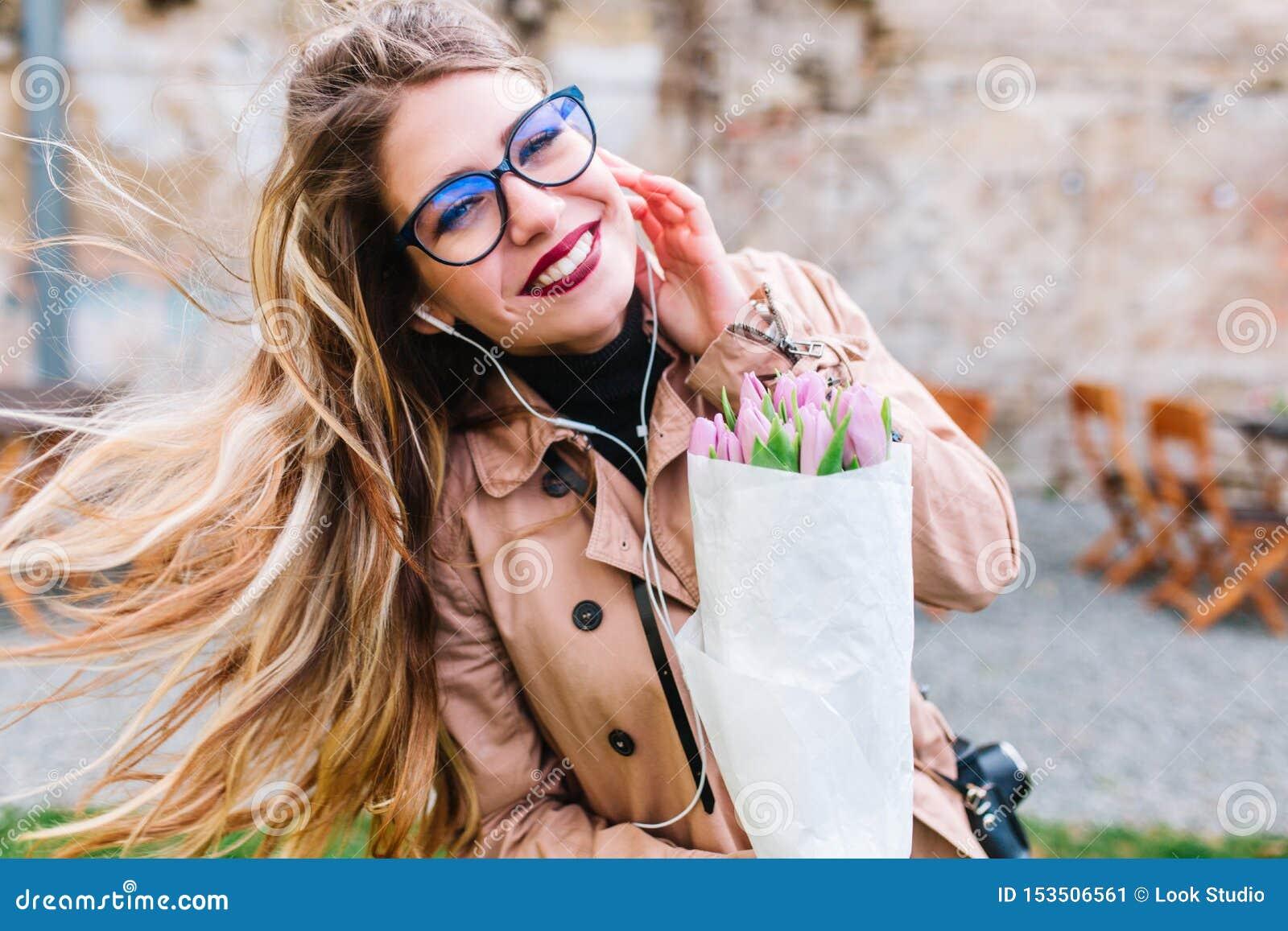 Retrato exterior do close-up da menina de sorriso bonita com o louro longo que flui o cabelo e as tulipas que vestem fones de ouv