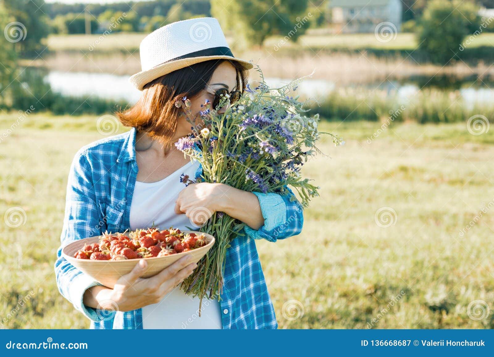 Retrato exterior do verão da mulher adulta com morangos, ramalhete dos wildflowers, chapéu de palha e óculos de sol Fundo da natu