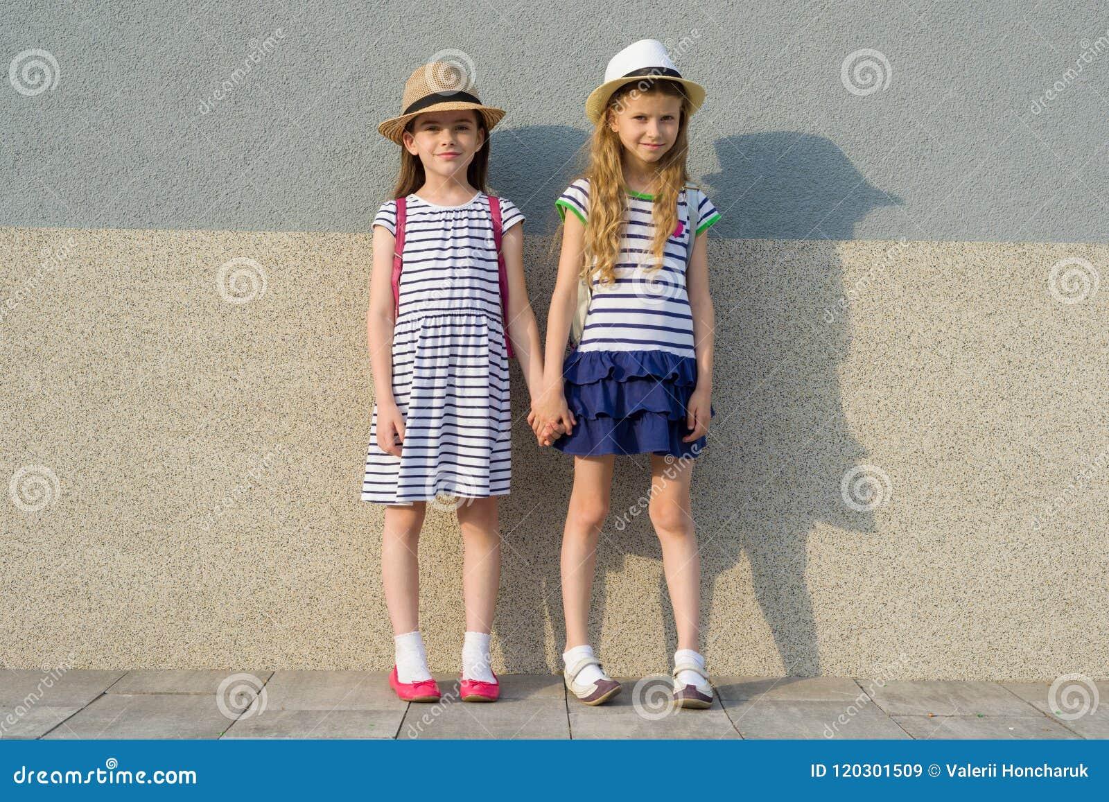 Retrato exterior do verão de duas namoradas felizes 7, 8 anos que guardam as mãos Meninas nos vestidos listrados, chapéus com tro