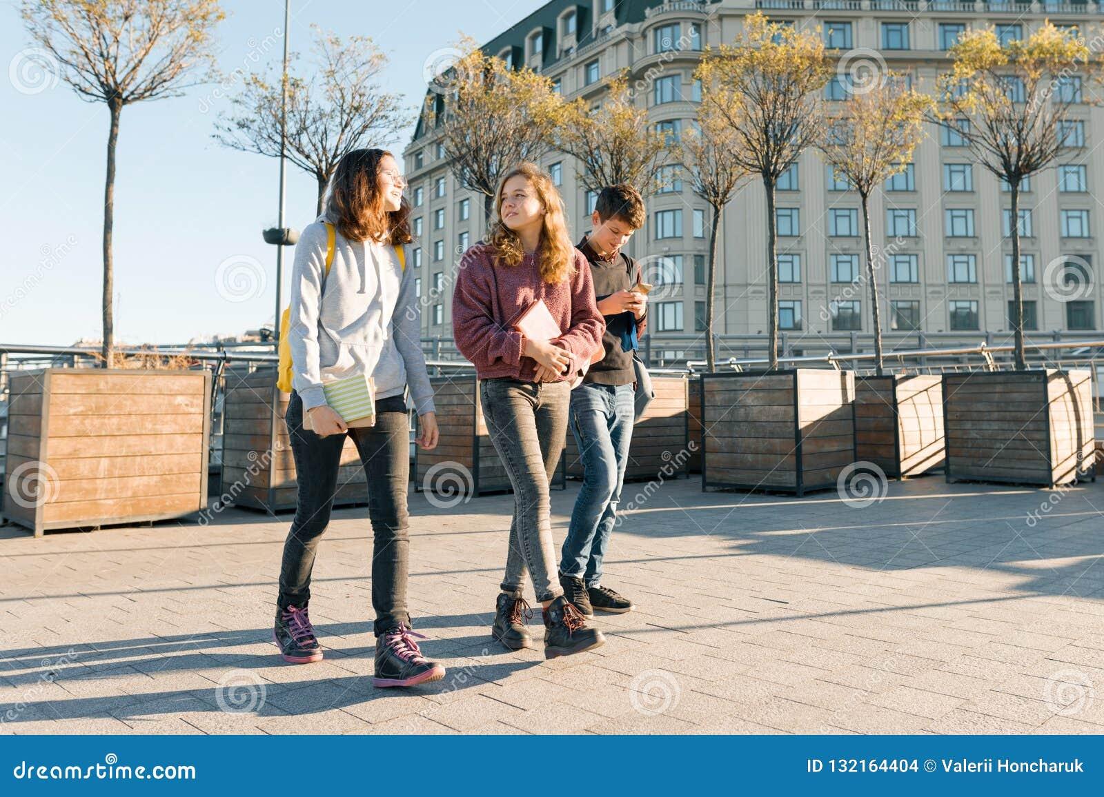 Retrato exterior dos estudantes adolescentes com trouxas que andam e que falam Fundo da cidade, hora dourada