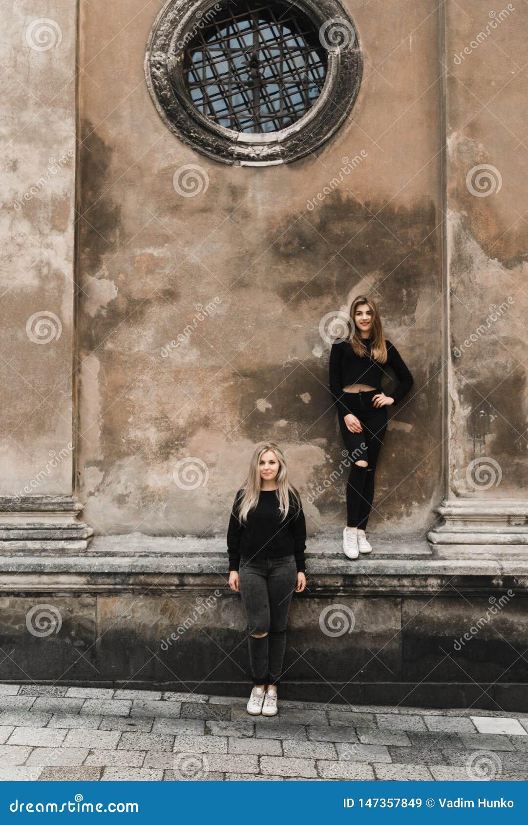 Retrato exterior dos jovens adolescentes bonitos felizes que viajam na cidade europeia velha, Lviv, Ucr?nia