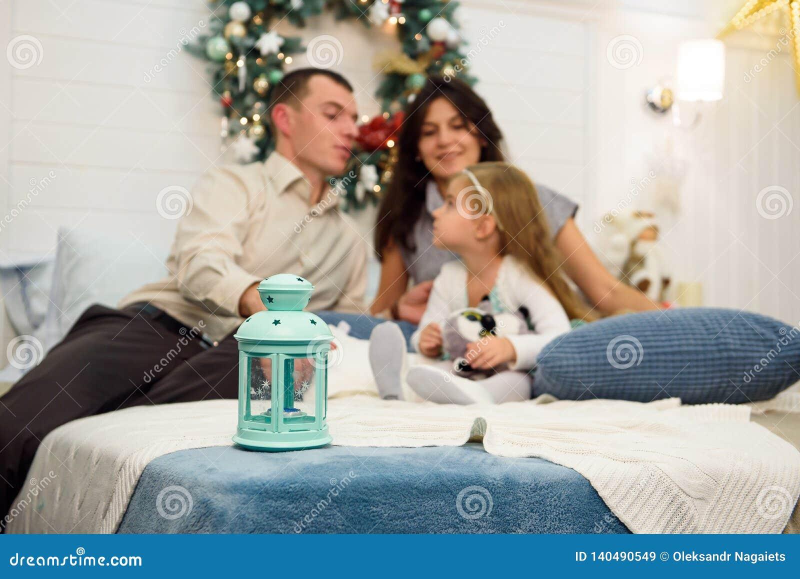 Retrato feliz da família no Natal, na mãe, no pai e na criança sentando-se na cama em casa, decoração dos chritmas em torno deles