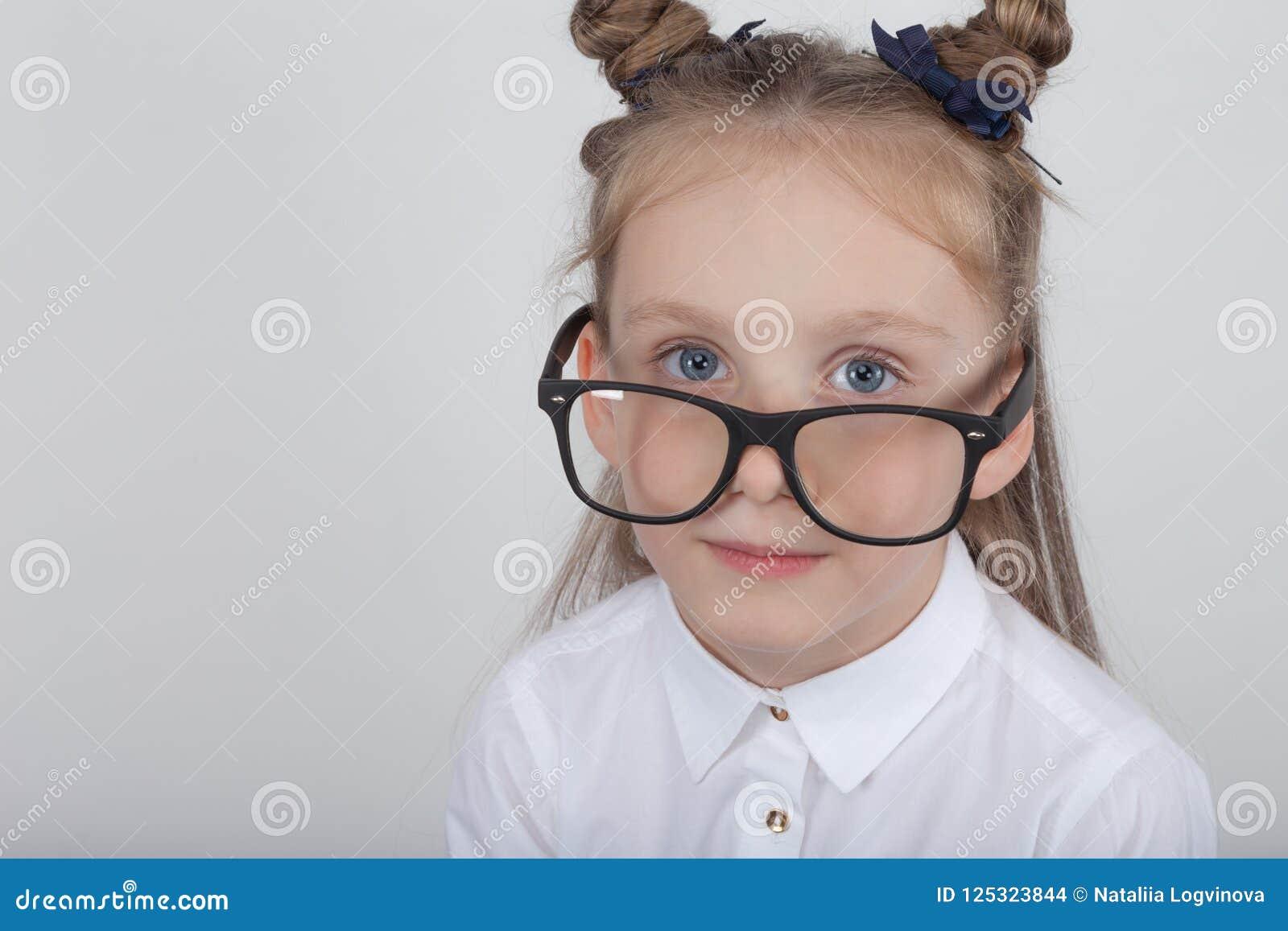 Retrato feliz de la niña, blusa blanca que lleva y lentes negras del marco, oponiéndose al fondo de madera blanco De nuevo a sch