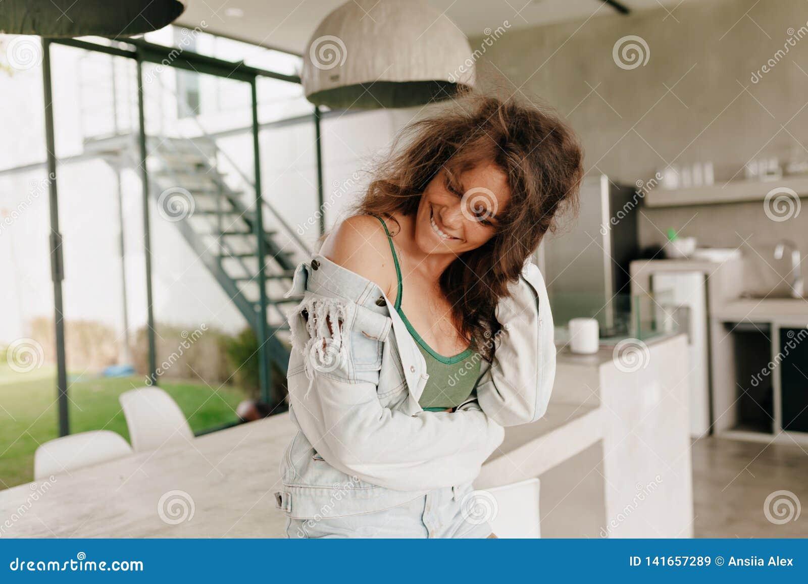Retrato feliz do estilo de vida de encantar a mulher feliz com o t-shirt do verão do cabelo encaracolado e o revestimento vestind