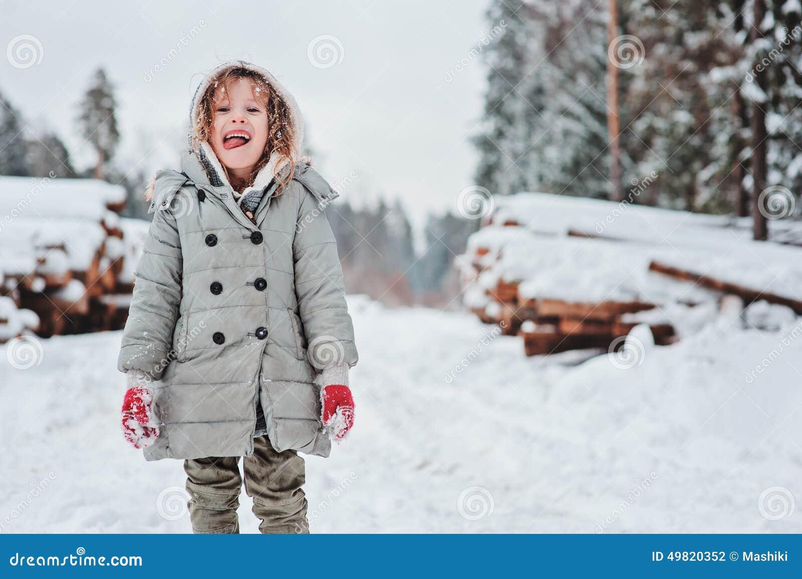 Retrato feliz engraçado da menina da criança na caminhada na floresta nevado do inverno com felling da árvore no fundo