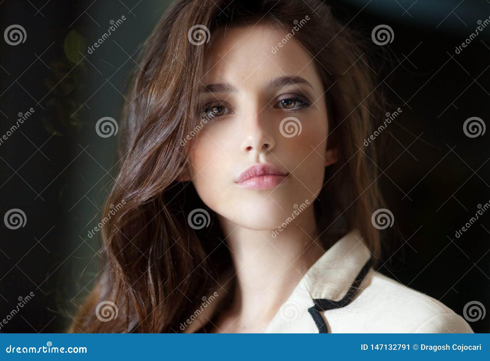 Retrato frontal de uma jovem mulher com cabelo longo, vestindo no terno delicado, olhando a câmera, fundo obscuro da sala