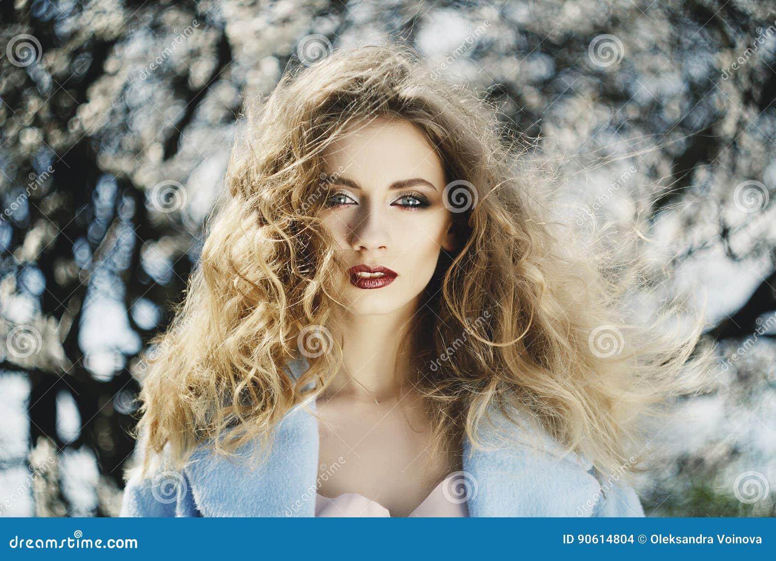 Retrato hermoso de la mujer joven en el jardín del flor en sprin