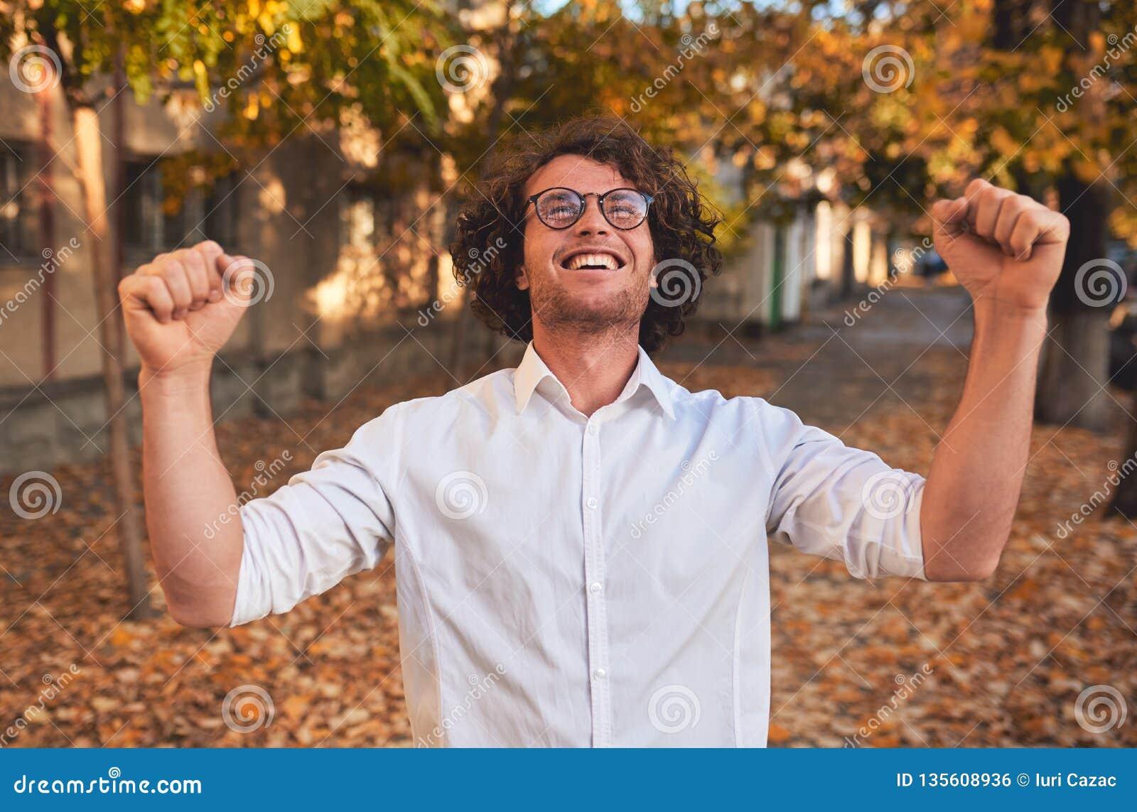 Retrato horizontal del primer del estudiante masculino o del hombre de negocios del ganador feliz con el pelo rizado que sonríe c