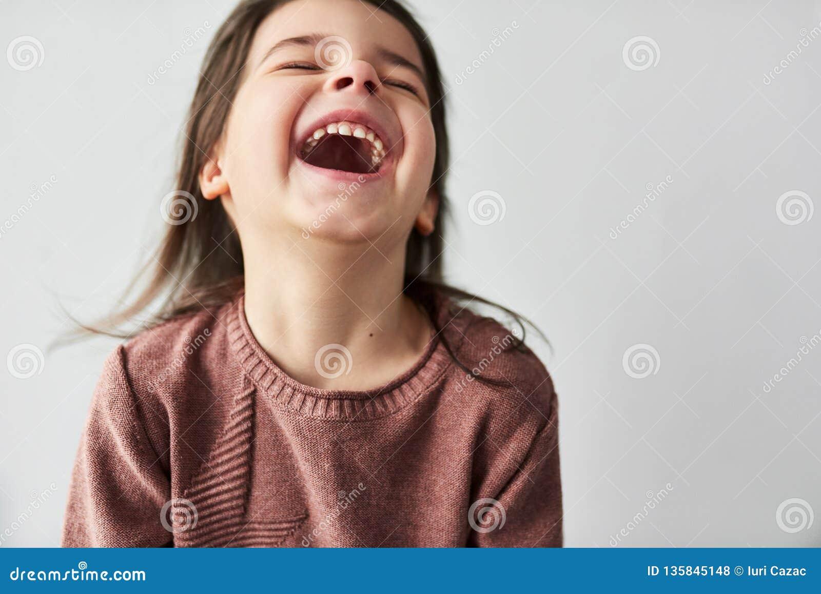Retrato horizontal do close up do estúdio da menina bonita feliz que sorri camiseta alegre e vestindo isolada em um estúdio branc
