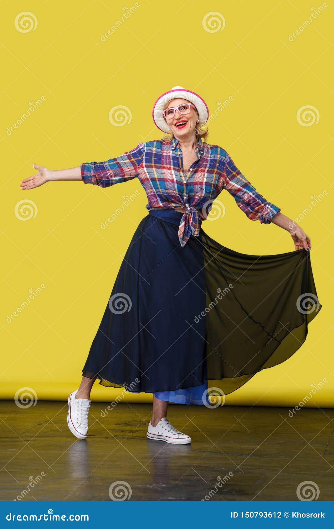 Retrato integral de la mujer madura elegante hermosa feliz en estilo sport con el sombrero y las lentes que se colocan, presentan